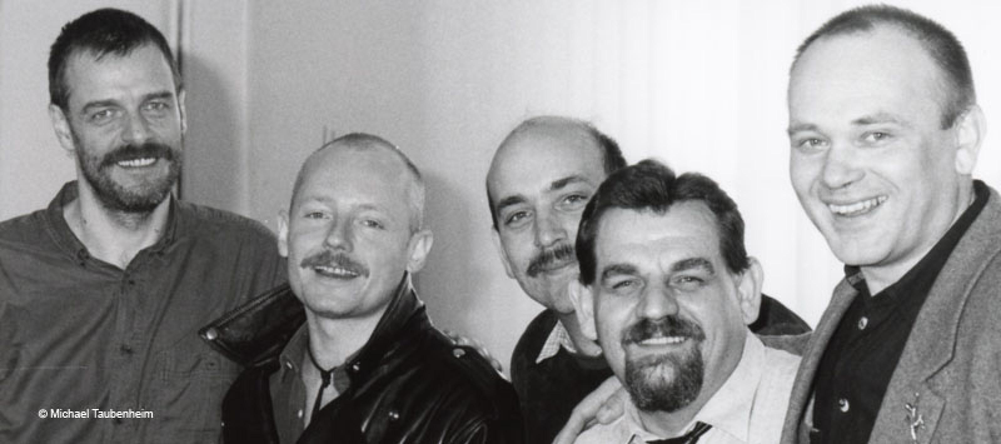 fünf Männer nebeneinander in einer Schwarz-Weiß-Fotografie