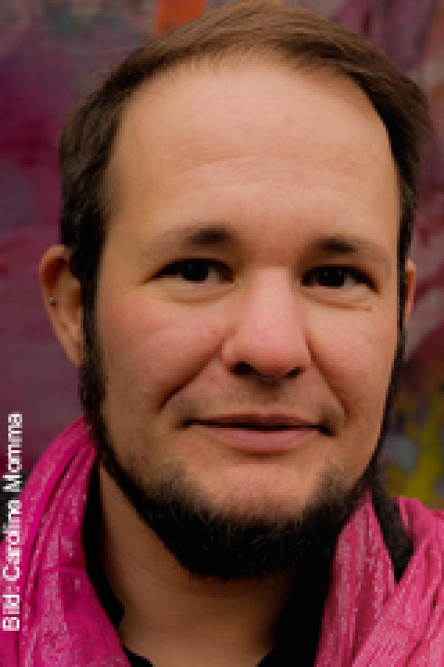 Mann mit Bart und rotem Schal