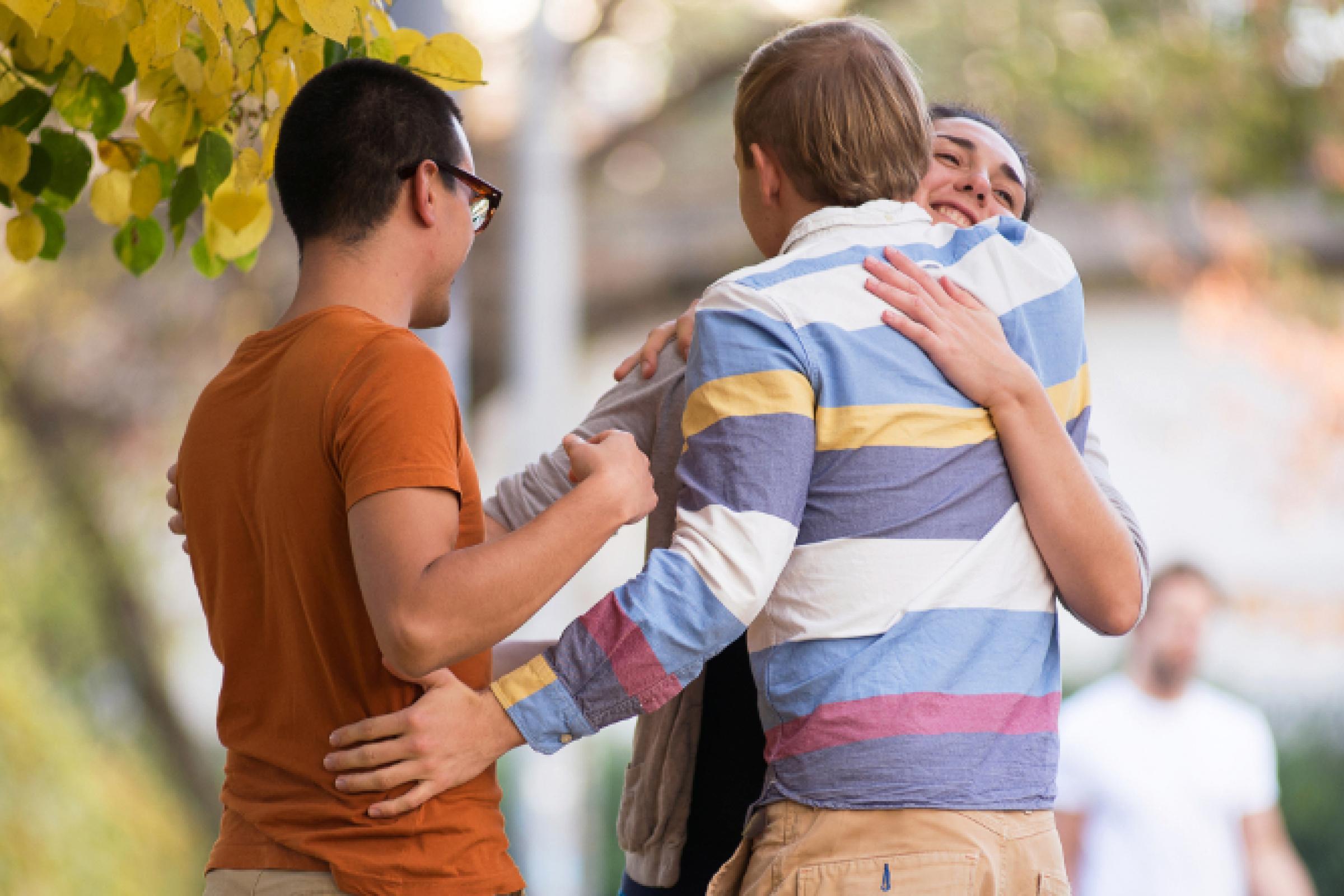 Drei Freunde umarmen sich