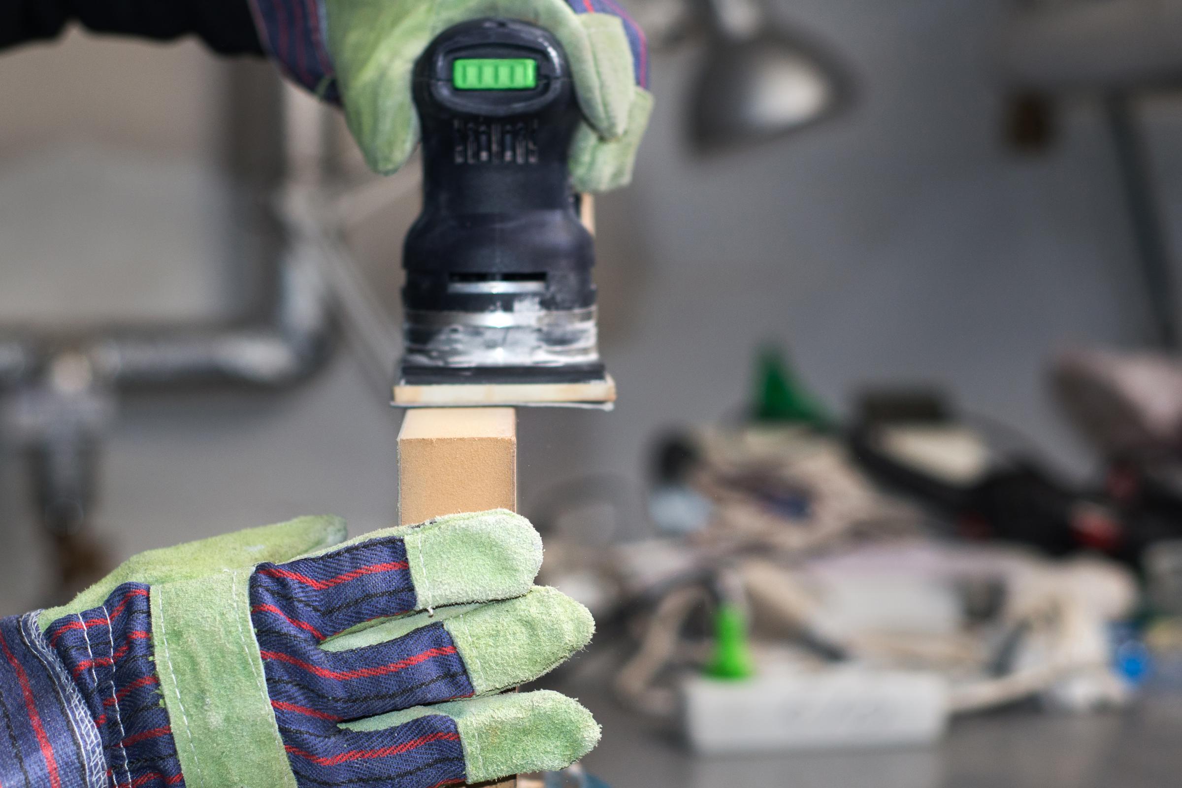 Nahaufnahme in einer Holzwerkstatt: Zwei Hände in Arbeitshandschuhen halten eine Schleifmaschine und bearbeiten damit ein Stück Holz