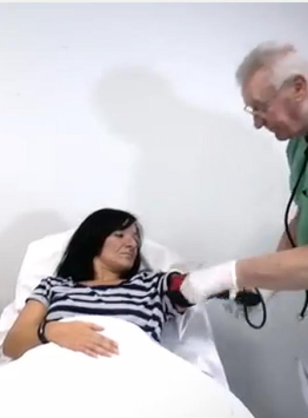 Eine Patientin liegt in einem Krankenhausbett