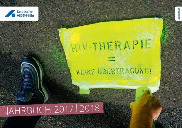 """Asphalt, Füße und Hand einer Person, welche mit einer gelben Farbdose und einer Schablone den Text """"HIV-Therapie = keine *Übrtragung"""" auf den Boden sprüht"""