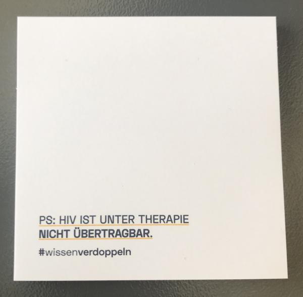 """Haftnotizblock. Aufdruck: """"PS: HIV ist unter Therpaie nicht übertragbar. #wissenverdoppeln"""""""
