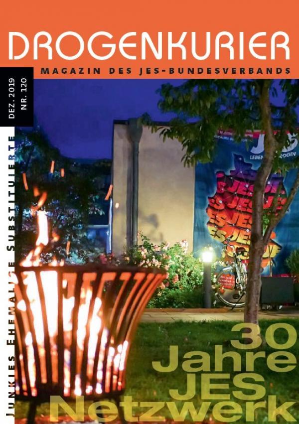 """Foto eines Feuerkorbes in einem Parkt. Im Hintergrund ein Plakat des JES Bundesverbandes. Titel """"Drogenkurier Nr. 120"""""""