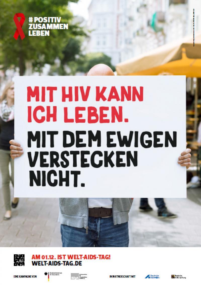 """Welt-Aids-Tag 2016, Person verdeckt mit Schild ihr Gesicht. Auf dem Schild steht """"Mit HIV kann ich leben. Mit dem ewigen Verstecken nicht."""""""