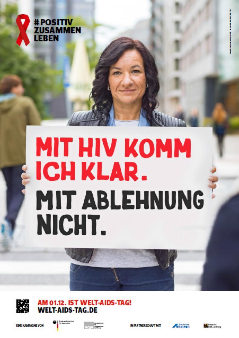 """Welt-Aids-Tag 2016, Frau hält Schild hoch mit dem Spruch """"Mit HIV komm ich klar. Mit Ablehnung nicht."""""""
