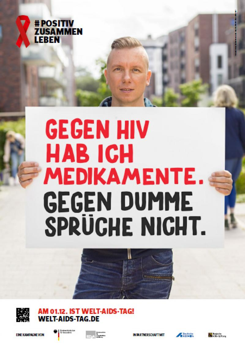 """Welt-Aids-Tag 2016, Mann hält Schild hoch mit dem Spruch """"Gegen HIV habe ich Medikamente. Gegen dumme Sprüche nicht."""
