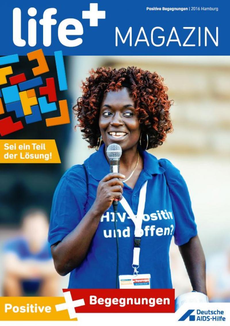 """Frau hält Mikrofon auf dem Podium. Sie trägt ein blaues T-Shirt mit der Frage """"HIV-positiv und offen?"""""""