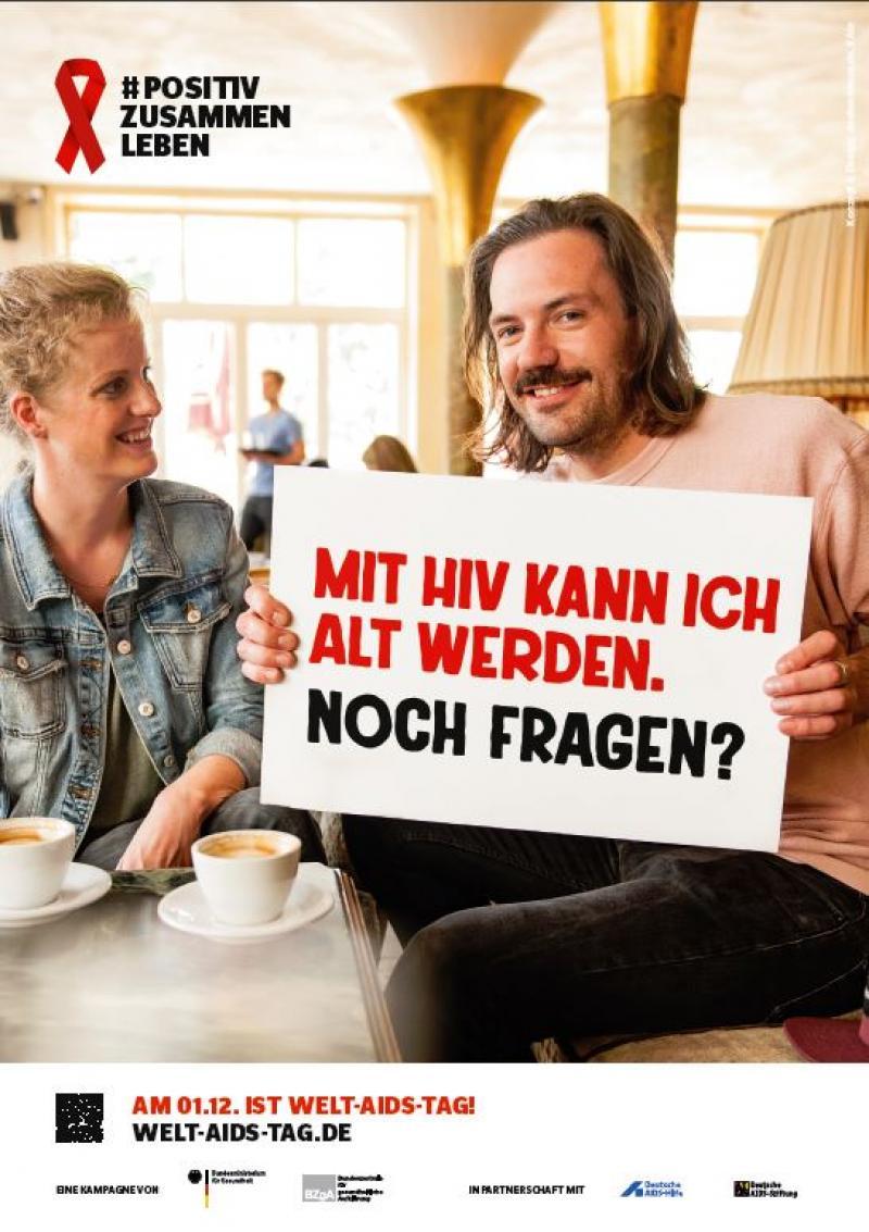 """Mann mit Schild in der Hand. Neben ihm eine Frau. Text auf dem Schild: """"Mit HIV kann ich alt werden. Noch Fragen?"""