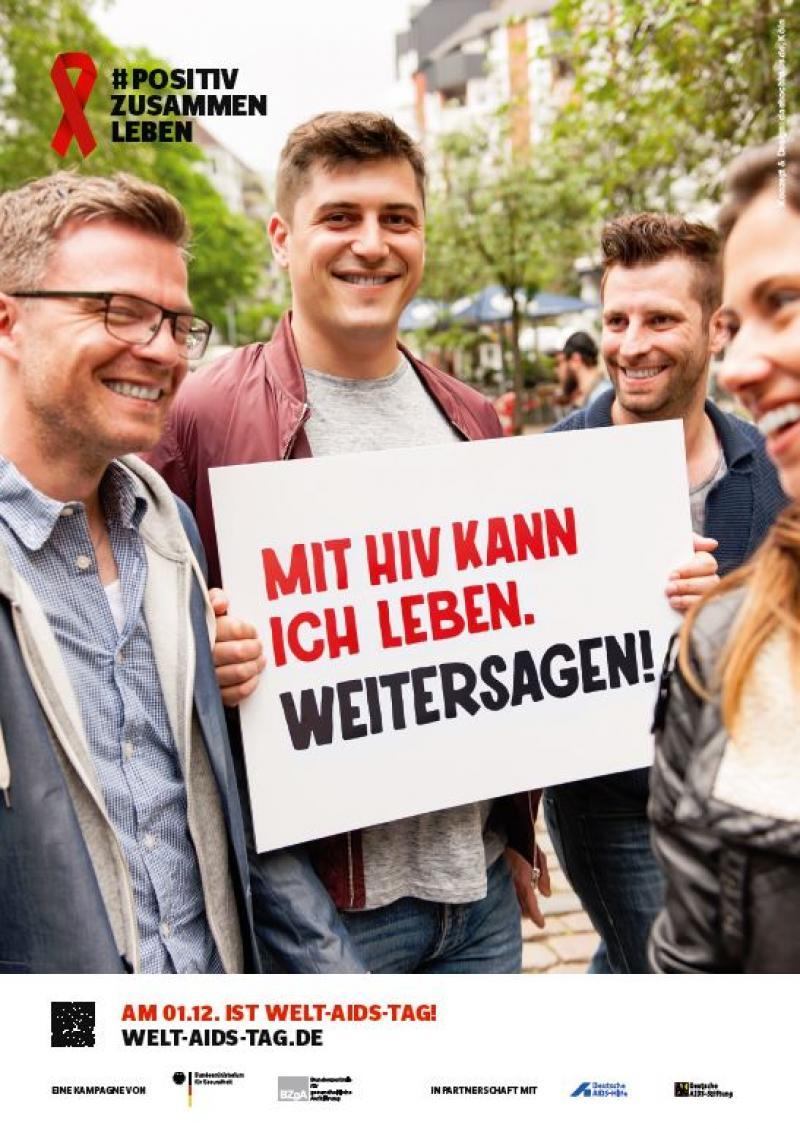 """Mann im Freundeskreis hält ein Schild hoch. Aufschrift: """"Mit HIV kann ich leben. Weitersagen!"""""""