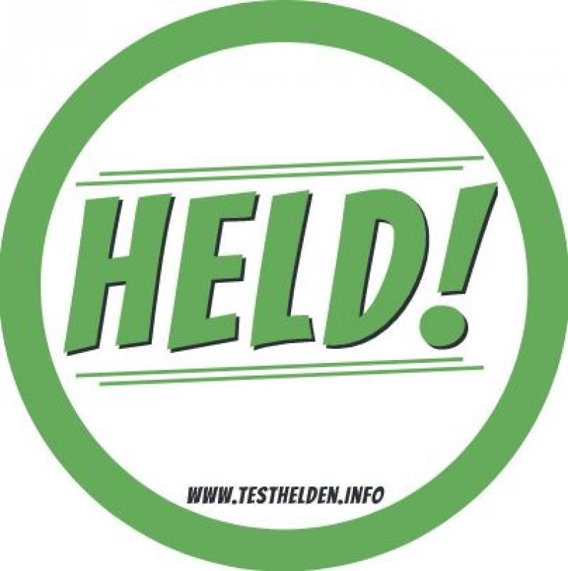 """Aufkleber aus der Kampagne """"Testhelden"""". Grüne Umrandung, in der Mitte der Spruch """"Held!"""""""