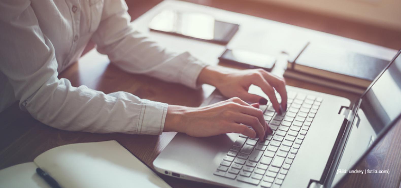 Frau sitzt am Schreibtisch mit Fingern auf der Tastatur