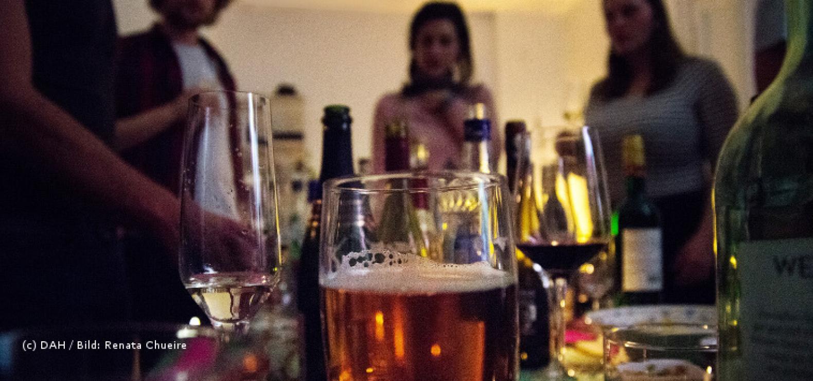 Blick auf eine Partyszene, im Vodergrund stehen mehrere alkoholische Getränke, im Hintergrund die Silhouetten von einigen Menschen