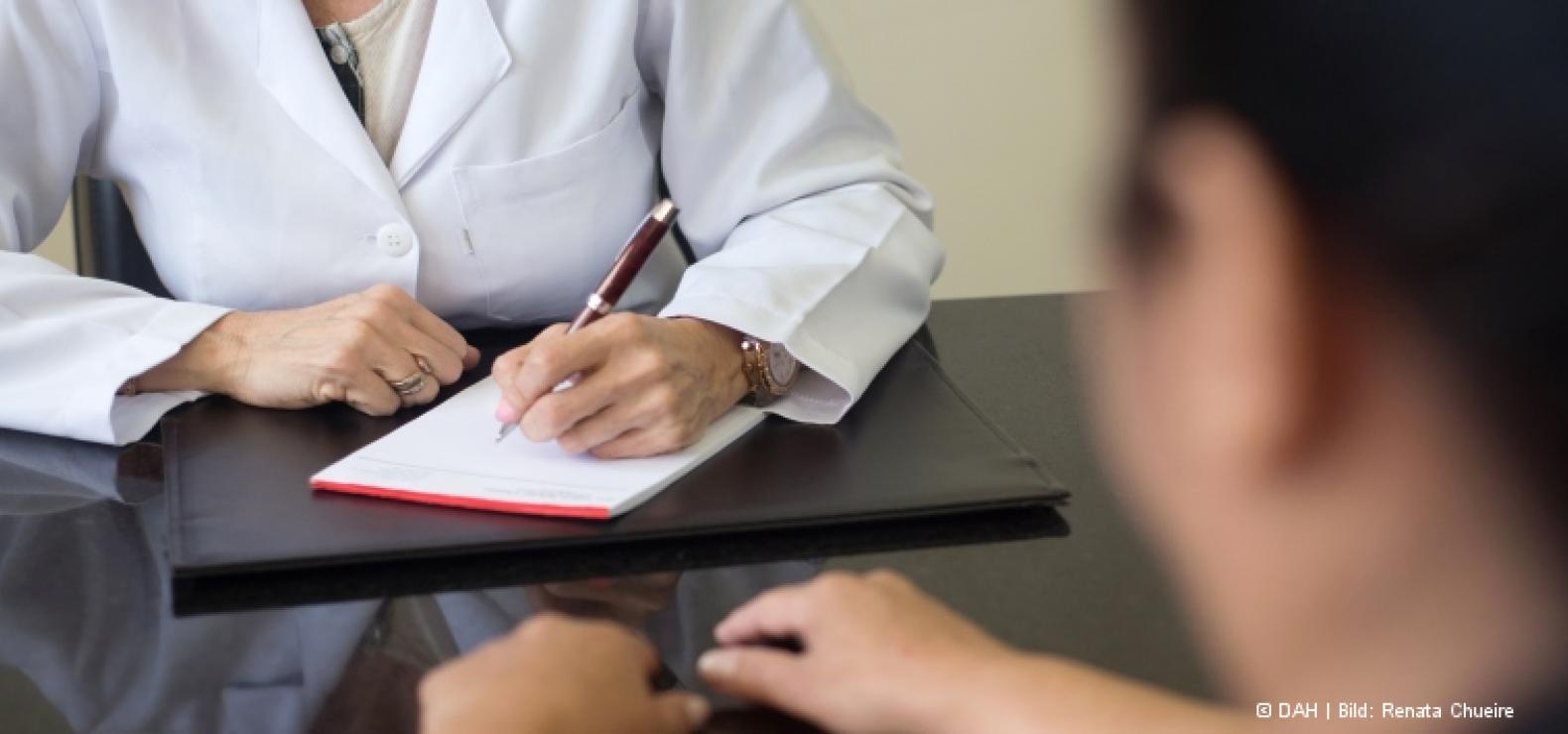 Ärztin und Patient sitzen sich gegenüber; die Ärztin macht Notizen