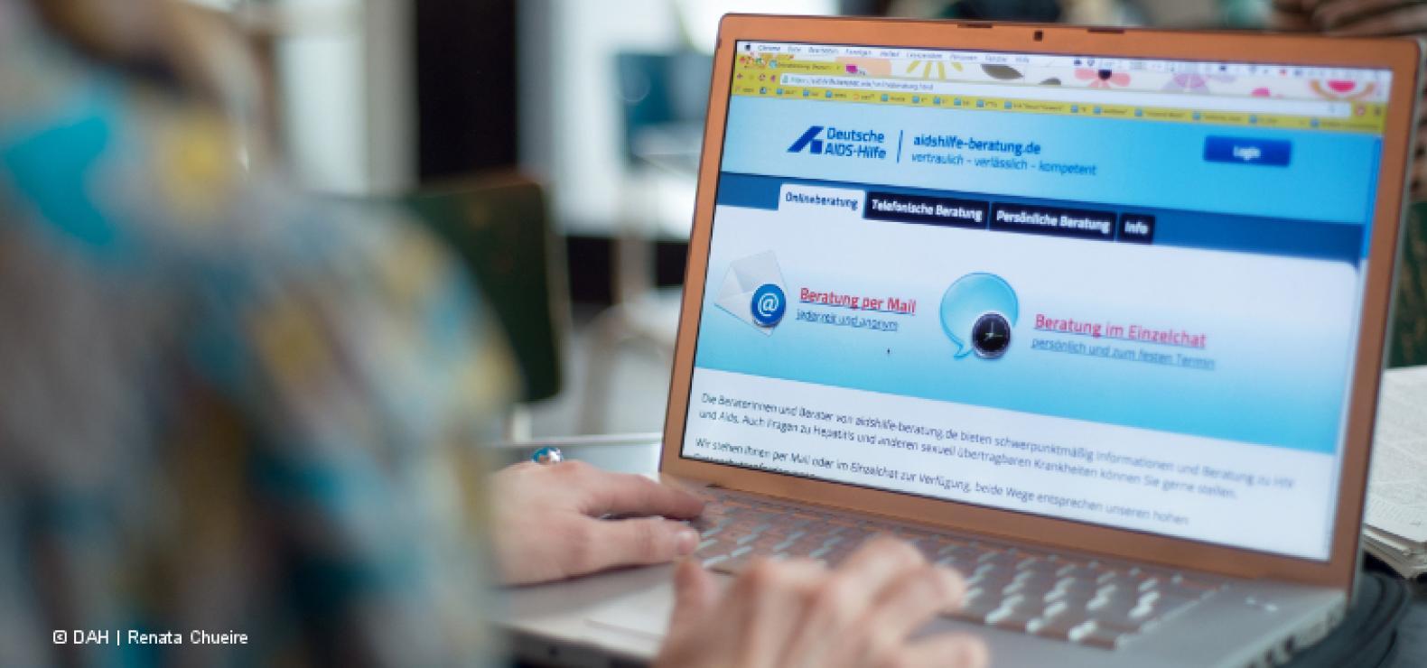 Person sitzt vor einem Laptop. Zu sehen ist die Website der Onlineberatung der Deutschen AIDS-Hilfe.