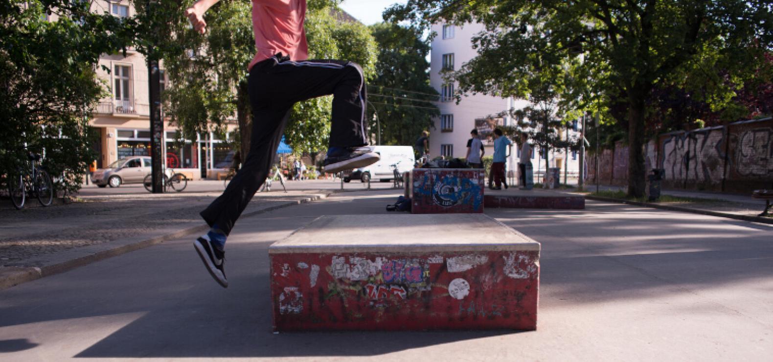 Ein Mensch springt über eine Hürde aus Stein, im Hintergrund ist eine Straßenszene zu sehen.