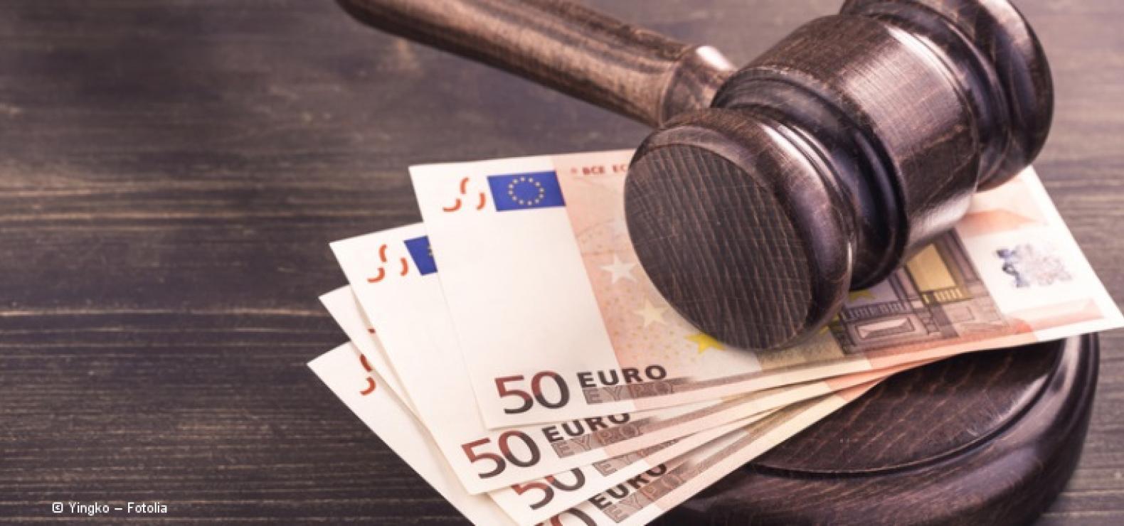 Brauner Gerichtshammer aus Holz, der auf 4 50-Euro-Banknoten abgelegt ist