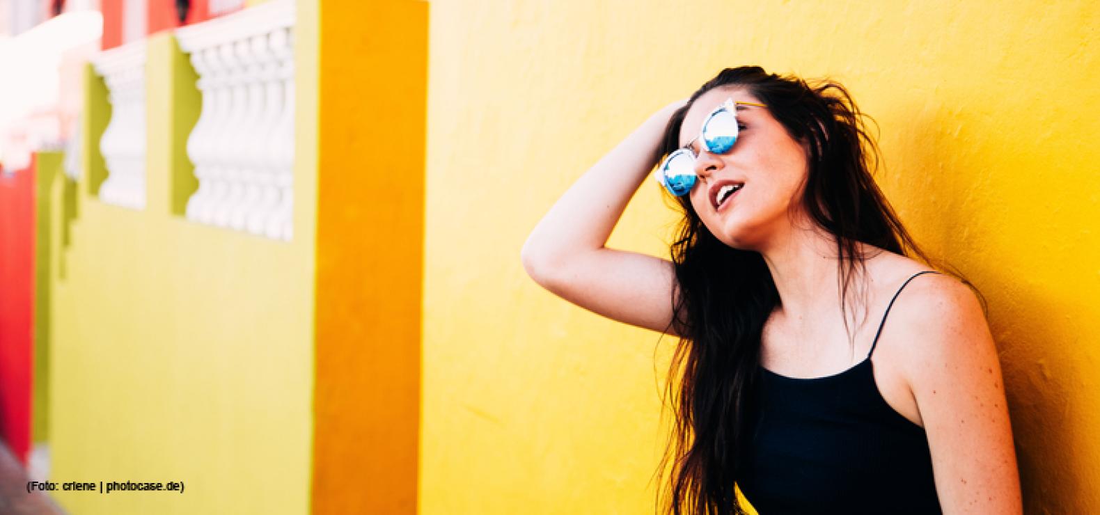 Frau mit Sonnenbrille lehnt an gelber Wand