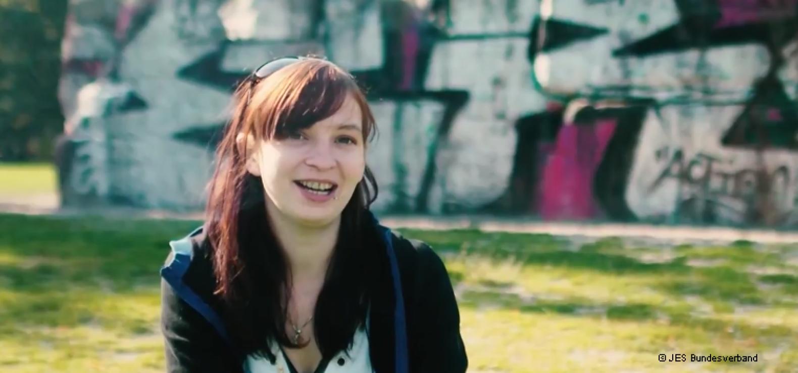 Junge Frau mit braun-rötlichen Haaren sitzt auf einer Wiese vor einer Graffiti-Wand