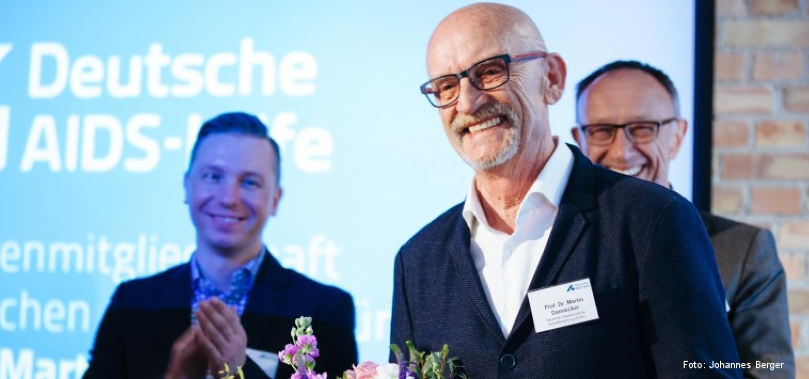 Im Vordergrund: ein lächelnder älterer Mann mit Glatze und dunkler Brille im Anzug, im Hintergrund zwei weitere lächelnde, applaudierende Männer im Anzug