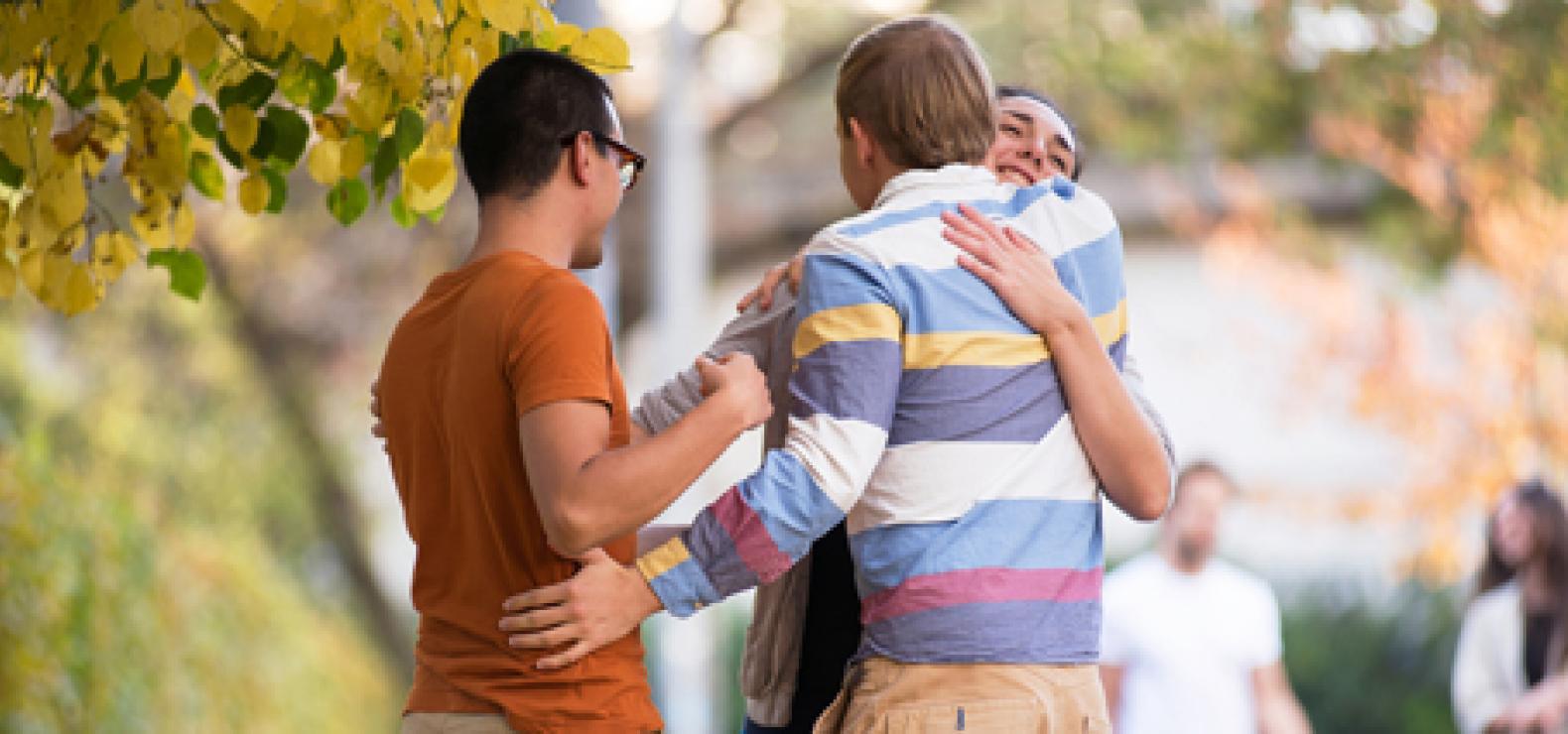 drei Menschen - zwei umarmen sich