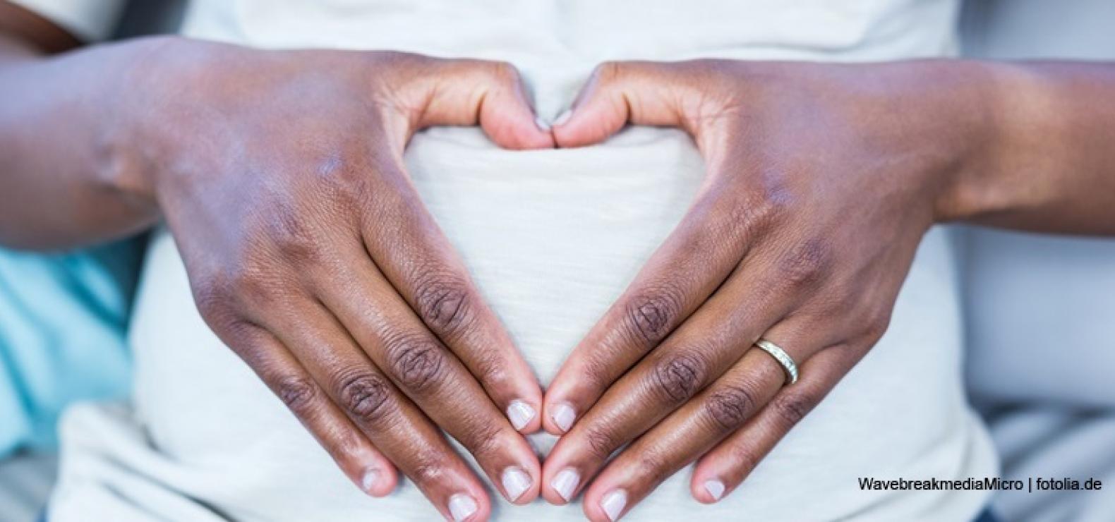 Schwangere Frau formt vor ihrem Bauch ein Herz mit ihren Händen.