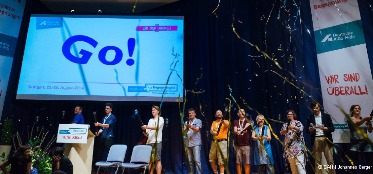 Auf einer Bühne stehen mehrere Menschen mit Konfetti-Kanonen, aus denen Girlanden geschossen werden. Im Hintergrund steht auf einer Projektionswand: Go!
