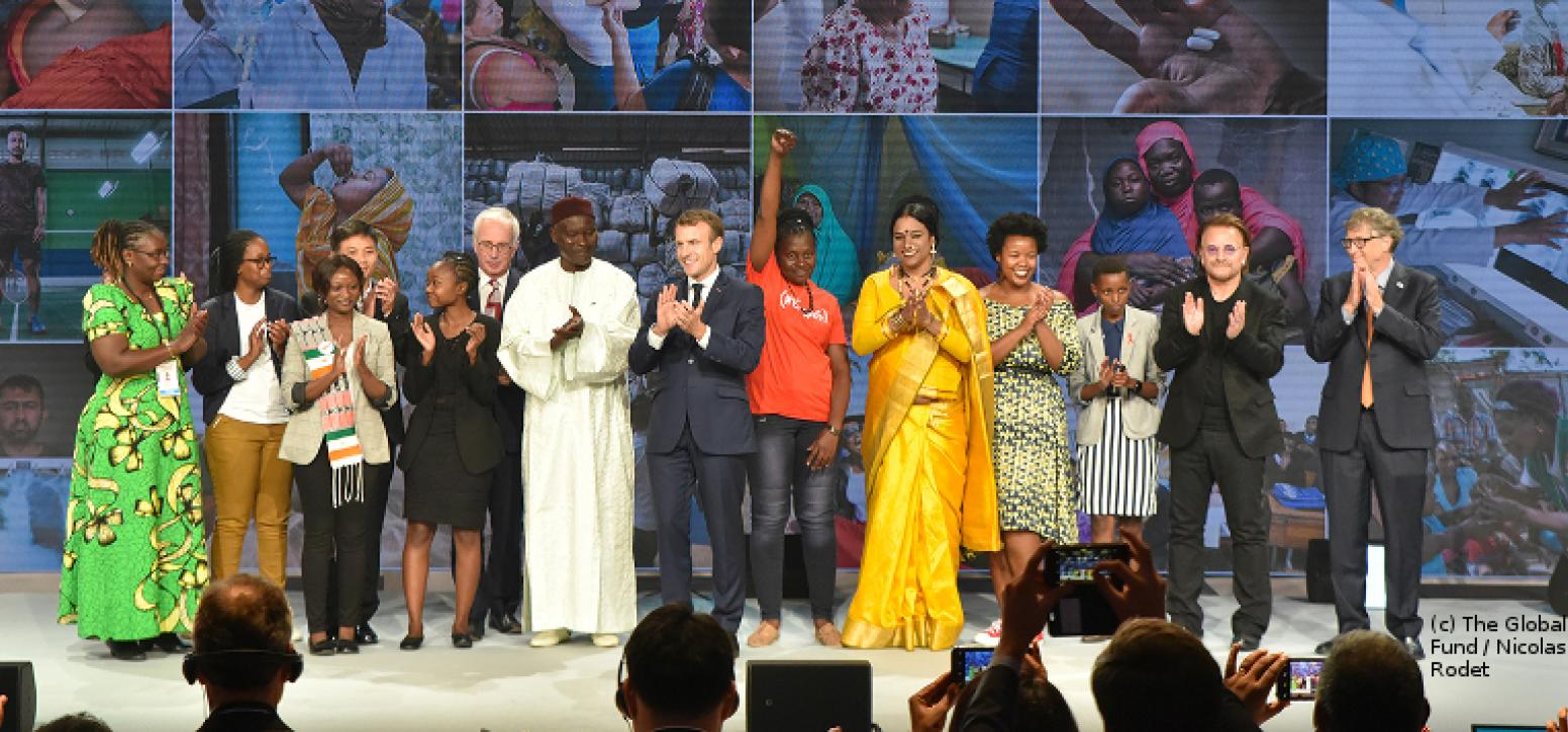 Politiker_innen und Vertreter_innen des Global Fund applaudieren auf einer Bühne