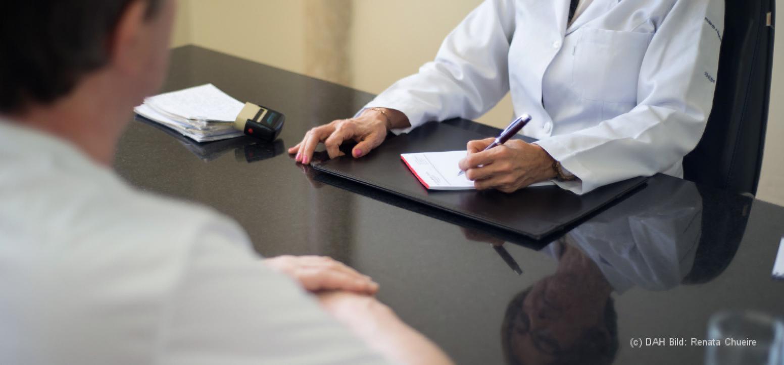 Ärztin sitzt an ihrem Schreibtisch und macht sich Notizen auf ihrem Block. Ihr gegenüber sitzt ein männlicher Patient.