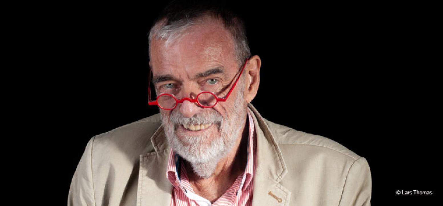 Mann mit grauem Bart, schaut lächelnd über rote Lesebrille