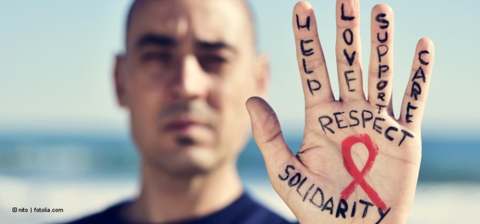 Mann streckt Handfläche zur Kamera. Darauf steht: Respect und Solidarity. In der Mitte die rote Aids-Schleife.
