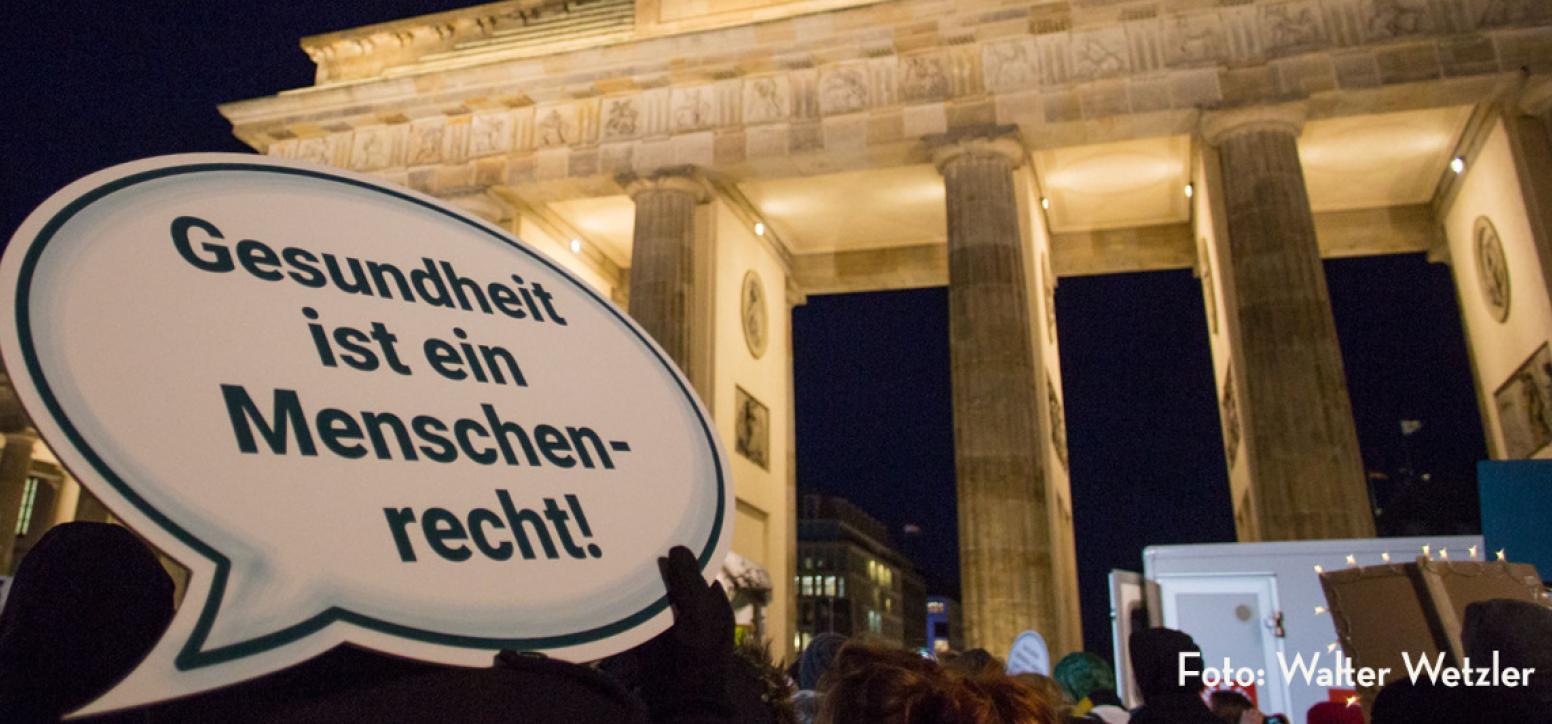 """Eine Demonstration am Brandenburger Tor in Berlin, im Vordergrund ein Schild mit der Aufschrift """"Gesundheit ist ein Menschenrecht"""""""