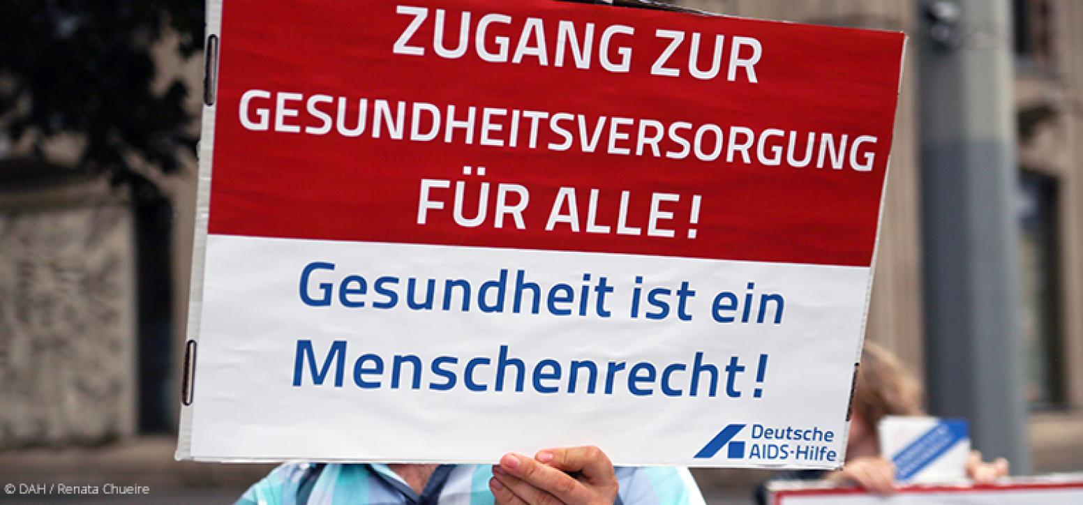 Schild auf Kundgebung mit Aufschrift: Zugang zur Gesundheitsversorgung für alle! Gesundheit ist ein Menschenrecht!