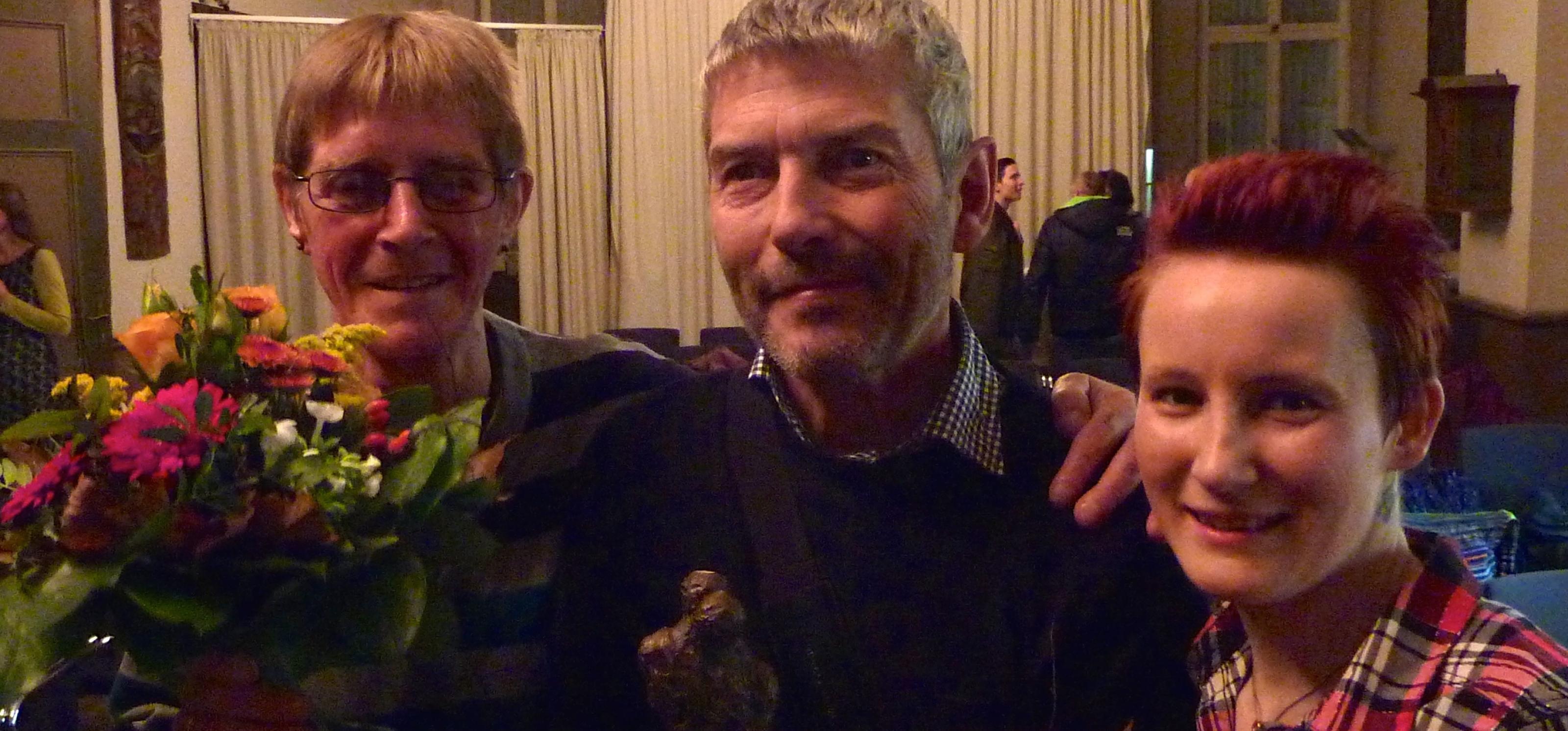 Drei der Preisträger mit Preisstatue und Blumen stehen unter einem Kronleuchter