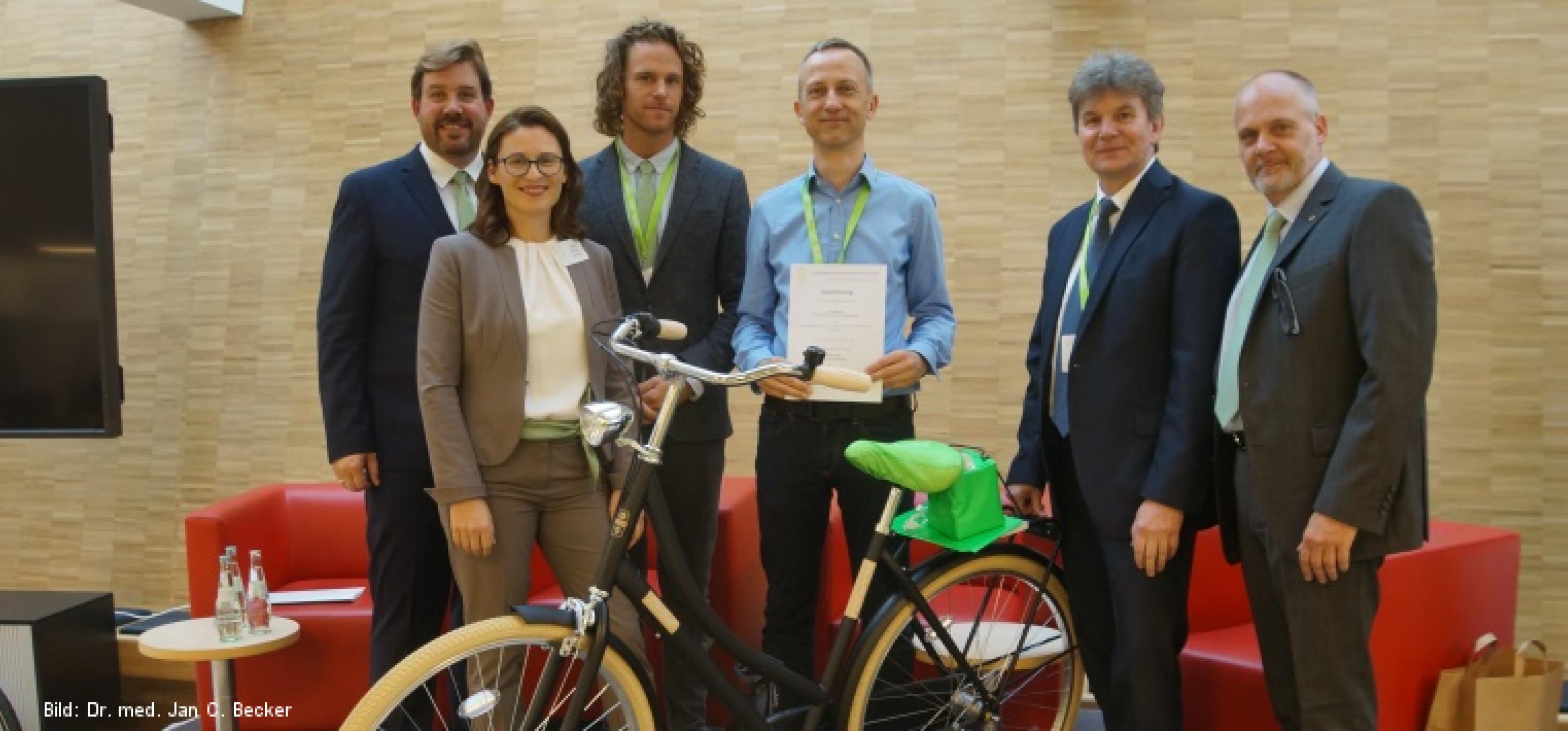 Sechs Personen nebeneinander, in der Mitte ein Mann mit Urkunde in der Hand, davor ein Fahrrad