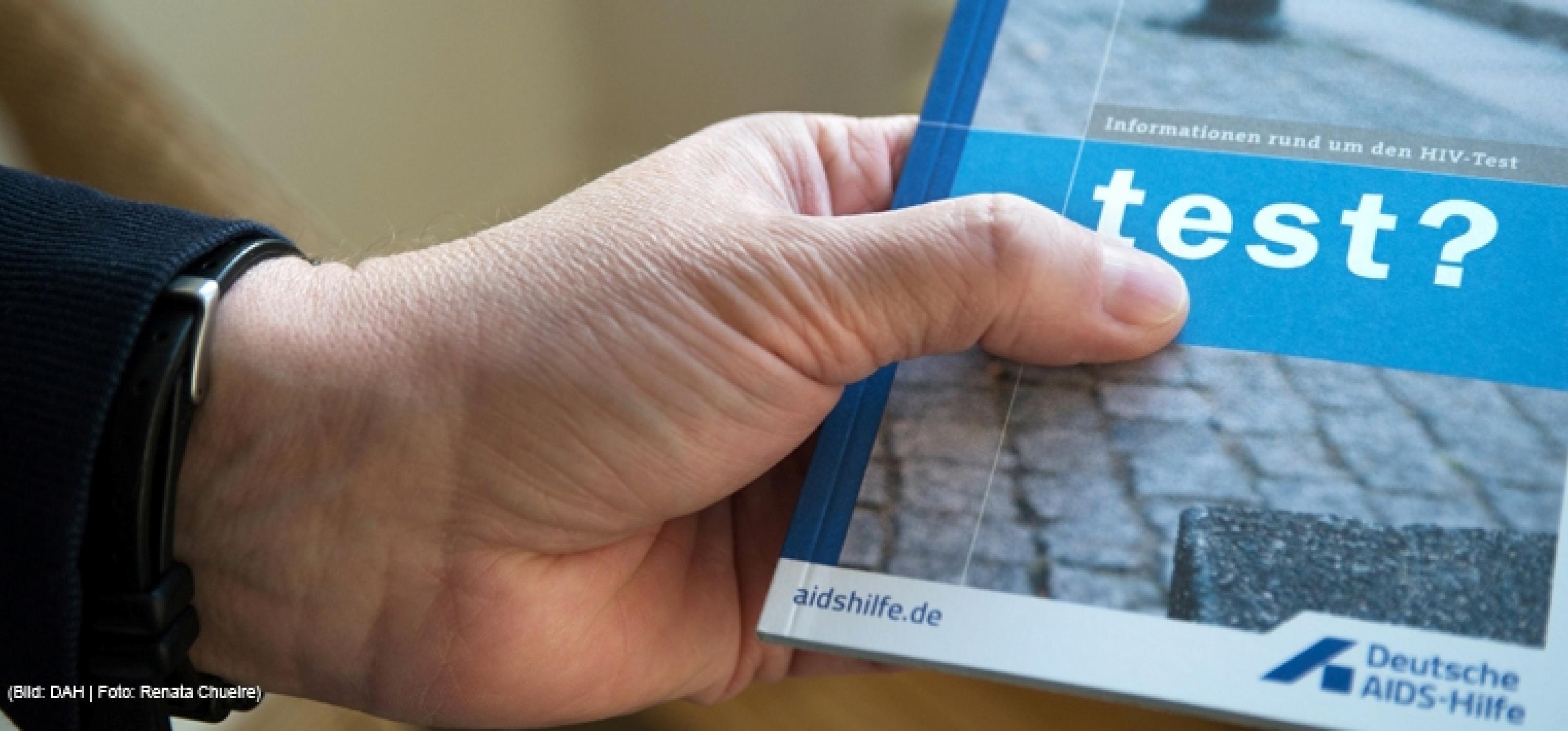 Hand hält eine Broschüre mit der Aufschrift test?