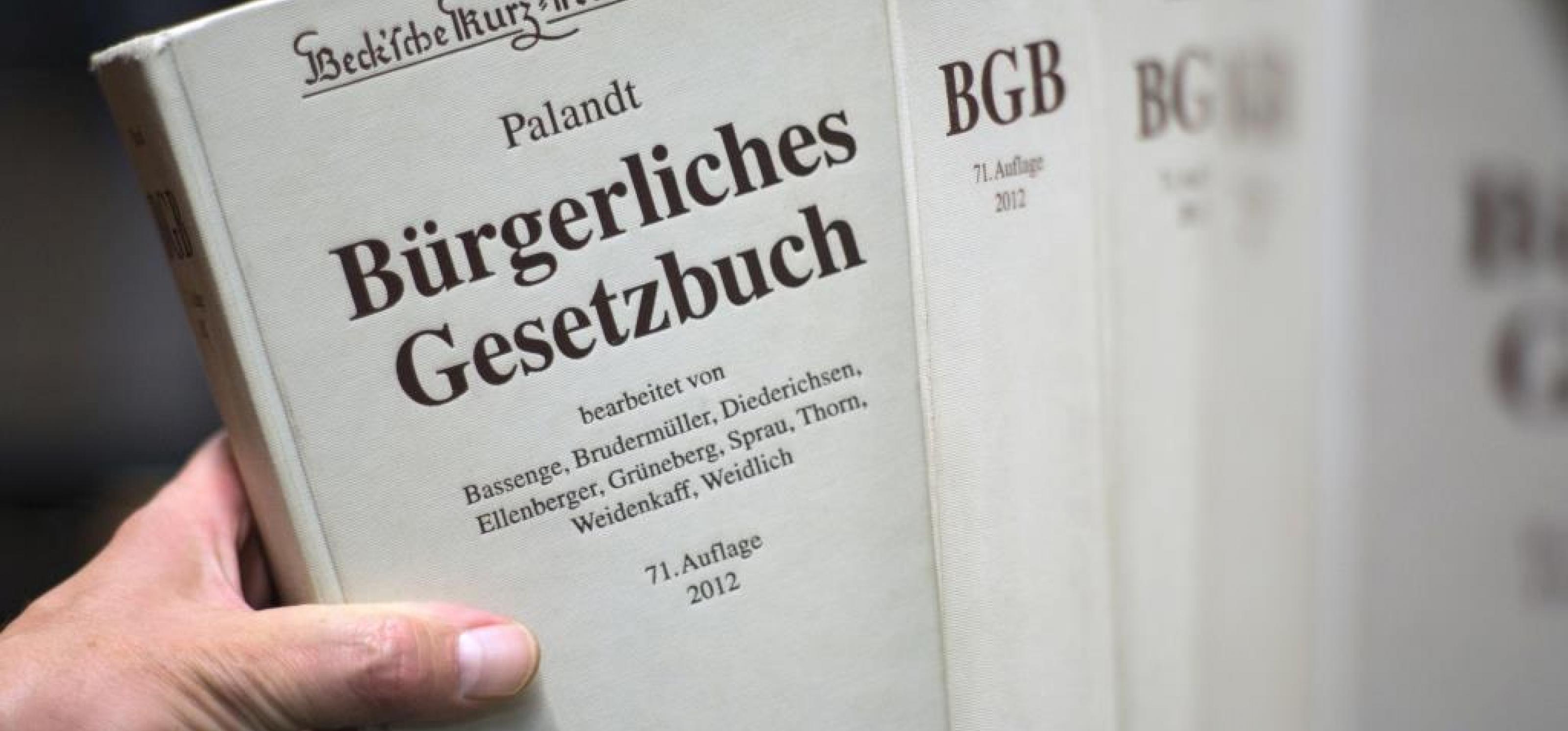 Eine Hand greift einen Band des Bürgerlichen Gesetzbuches aus einem Regal