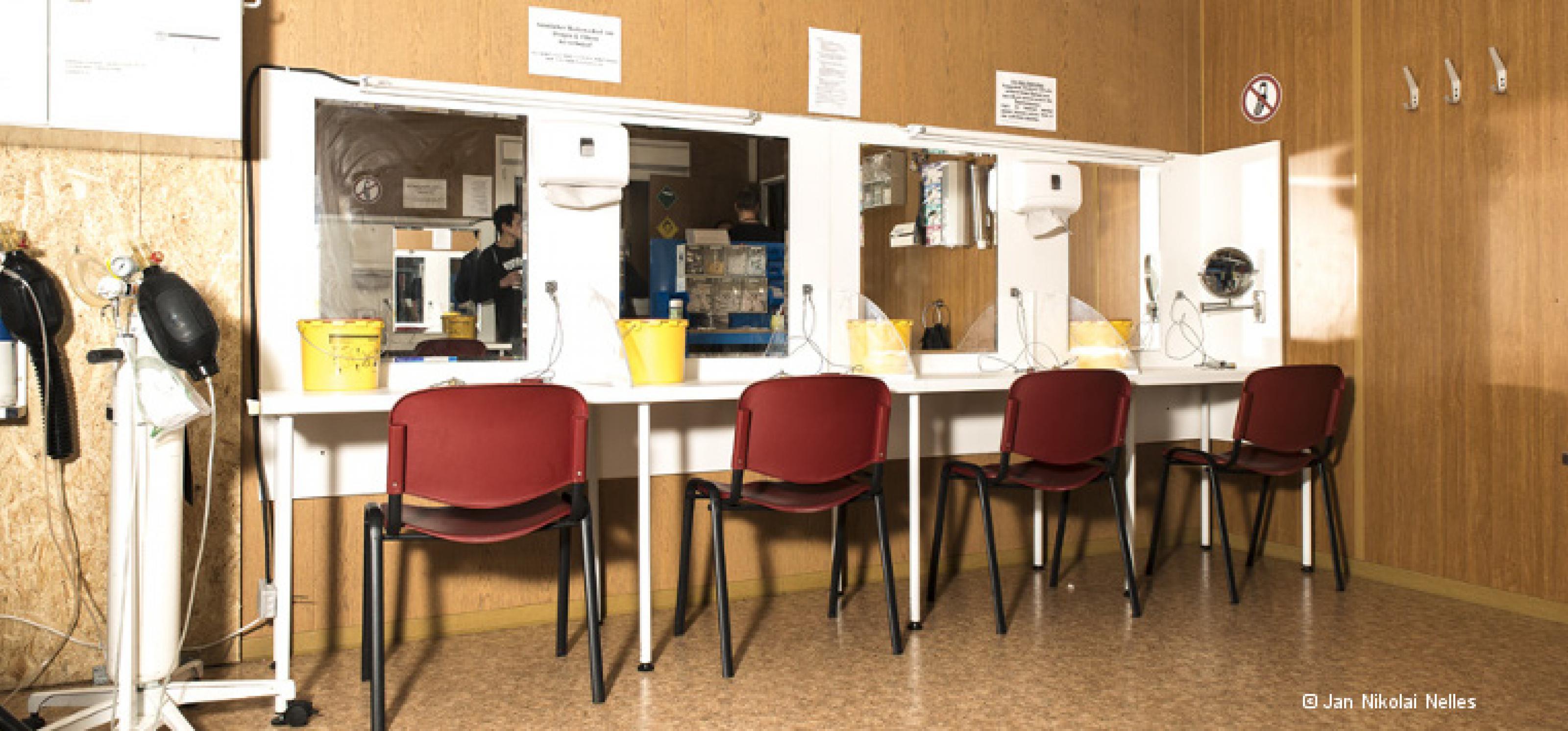 Drogenkonsumraum: Entlang einer Wand stehen vier Stühle vor Tischen und Spiegeln, an denen Drogen gespritzt werden können. An der Seite stehen zwei Beatmungsgeräte.