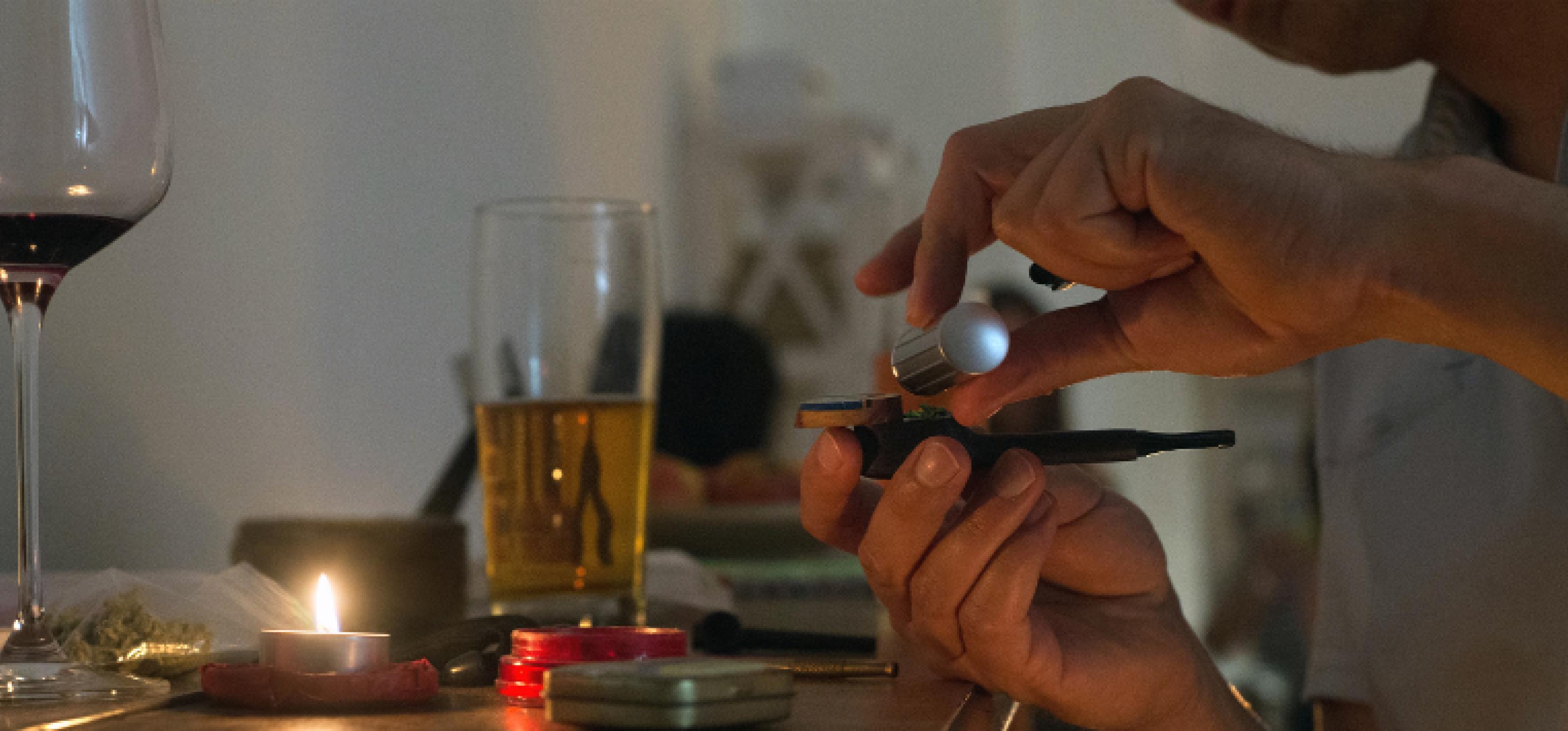 Zwei Hände befüllen eine Pfeife, im Hintergrund mehrere Gläser Alkohol, eine Pillendose und ein Tütchen