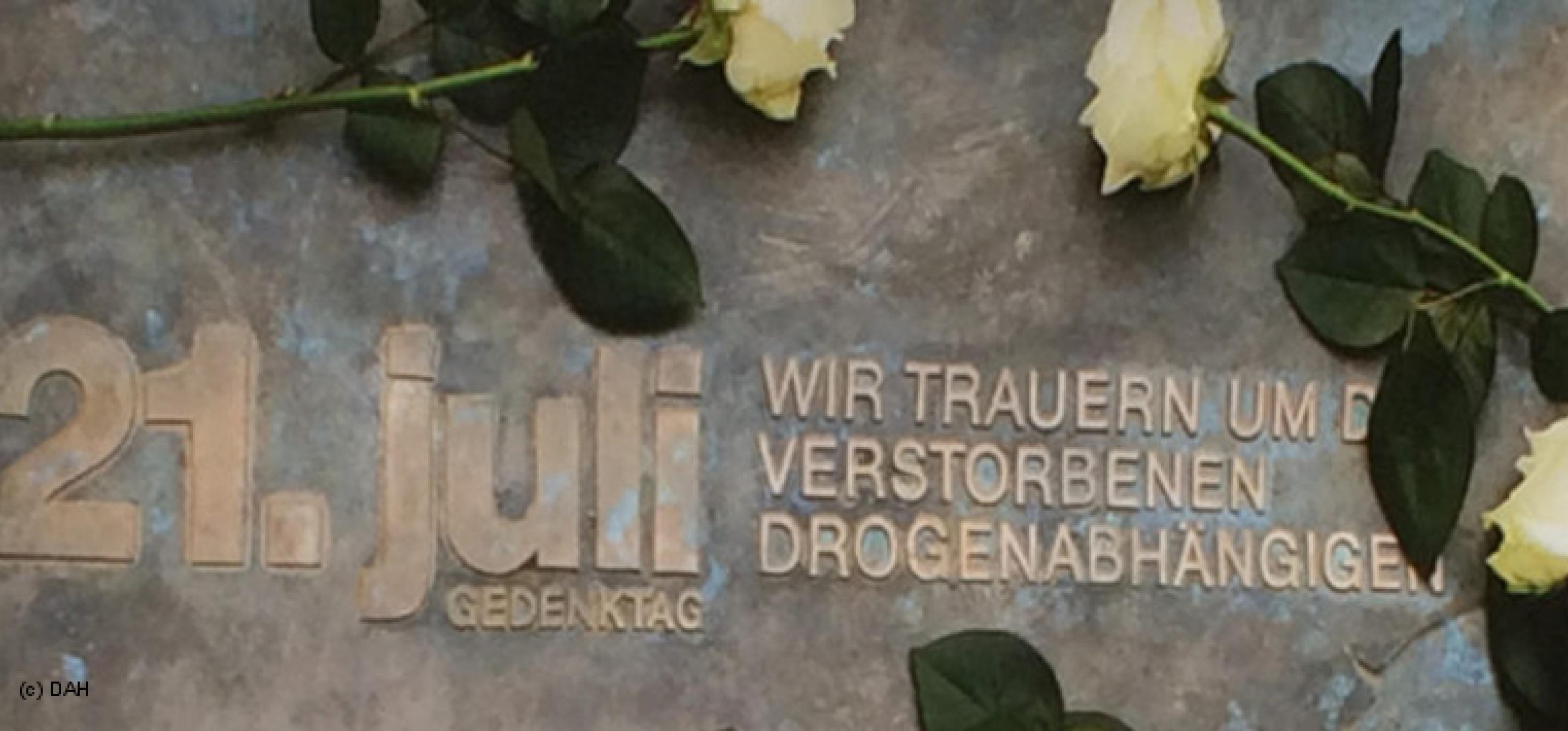 Zu sehen ist ein Gedenkstein mit der Aufschrift: 21. Juli, Gedenktag, wir trauern um die verstorbenen Drogenabhängigen. Frische weiße Rosen umrahmen die Aufschrift.
