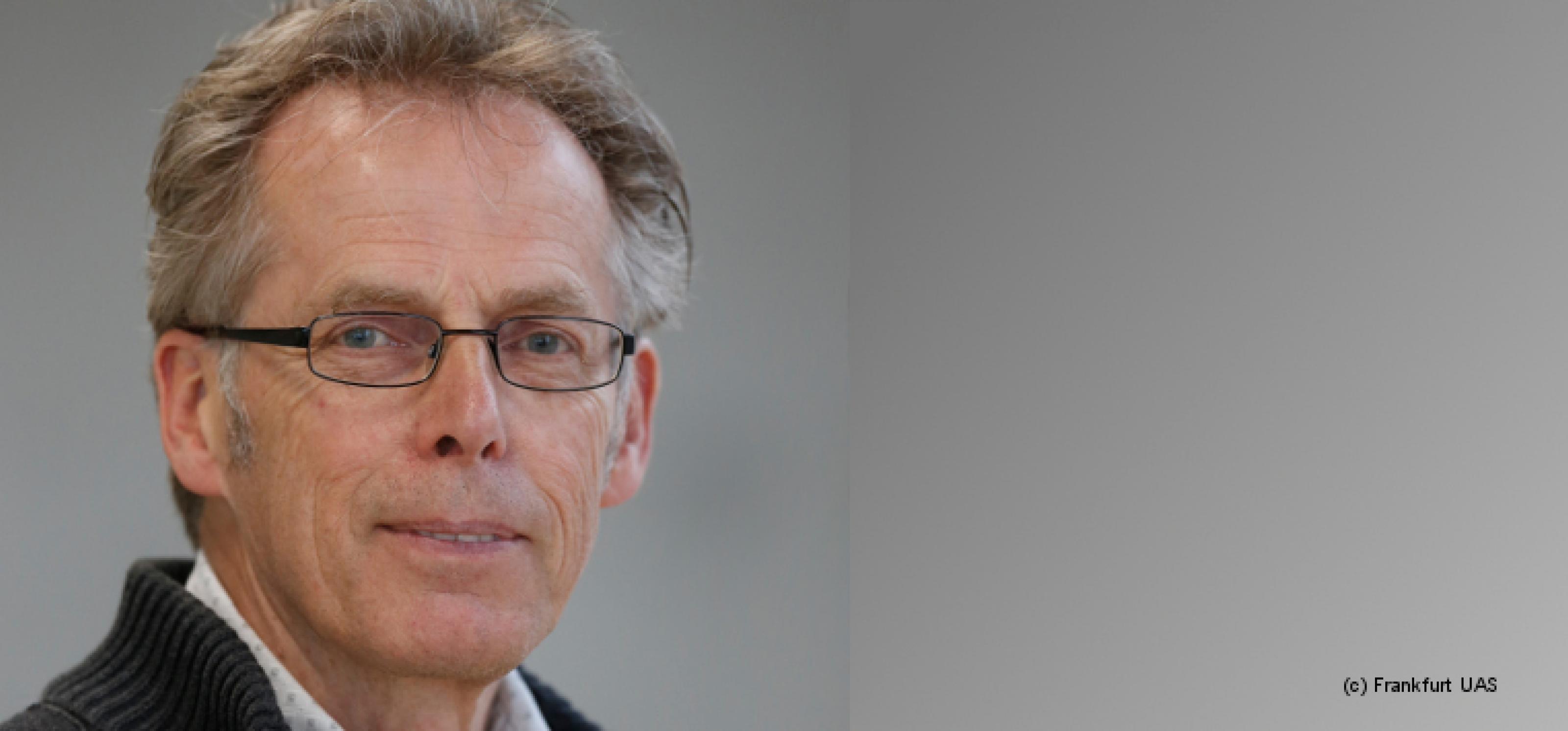 Porträt von Heino Stöver vor grauem Hintergrund