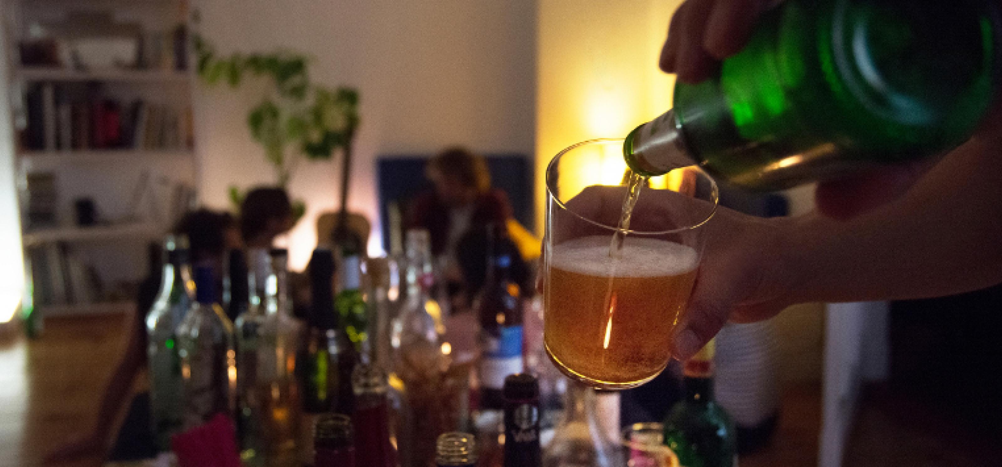 Eine Partyszene im Dämmerlicht, auf einem Tisch stehen verschiedene Gläser und Flaschen mit Alkohol