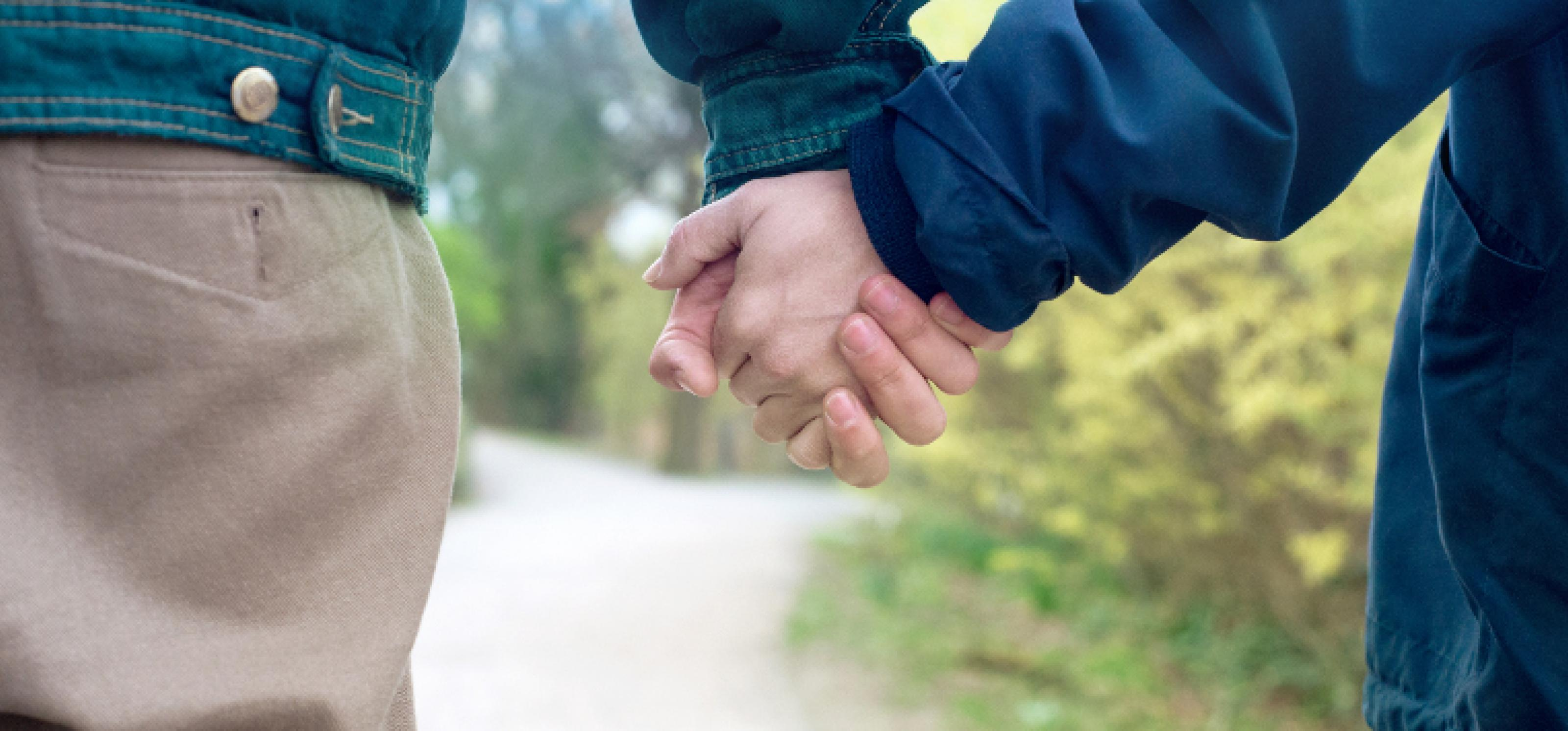 Zwei Menschen in Partnerschaft halten miteinander Händchen