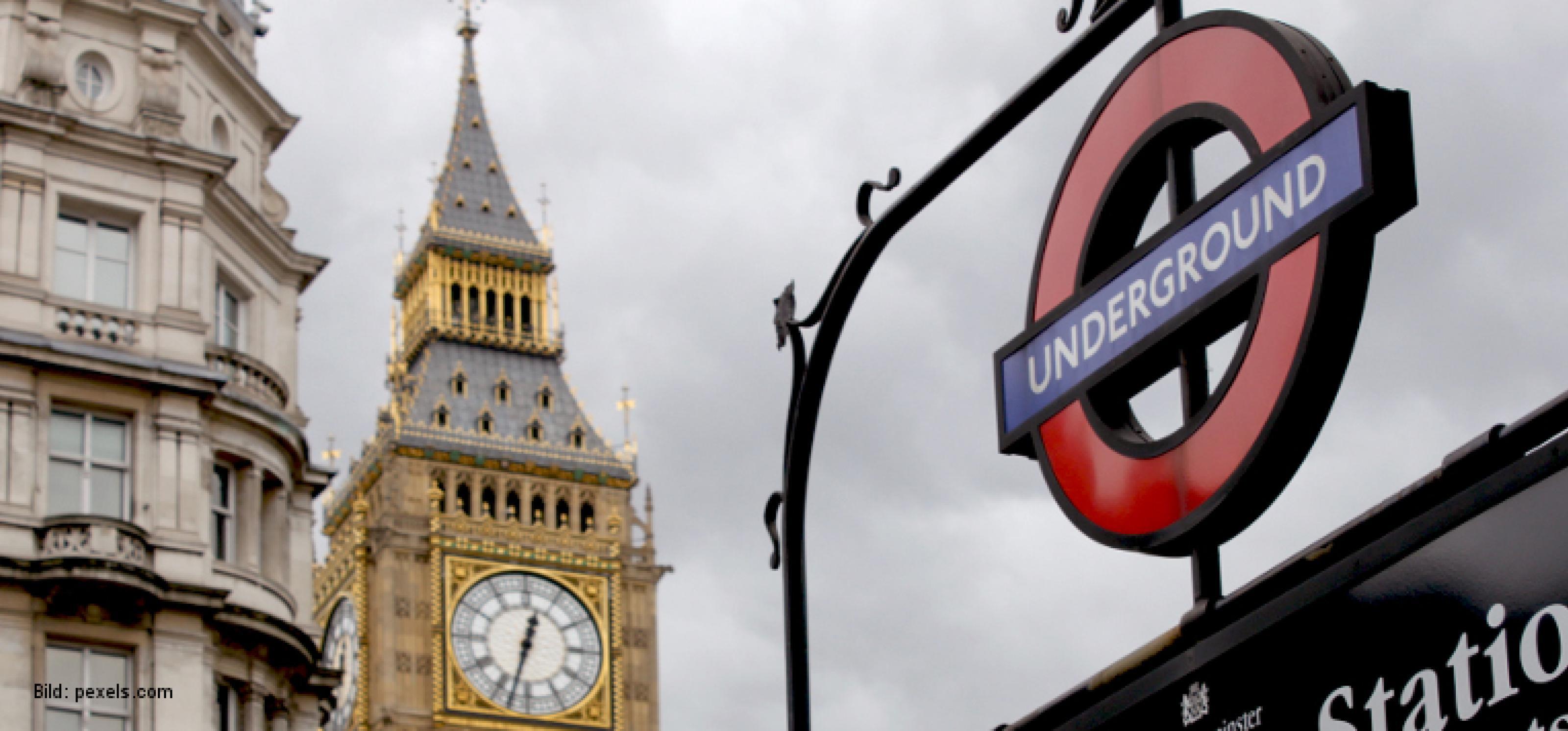 """Im Vordergrund ist das Schild zu einem Eingang der Londoner U-Bahn mit der Beschriftung """"Underground"""" zu sehen. Im Hintergrund sieht man den oberen Teil des Turms der Houses of Parliament mit der Uhr von Big Ben."""