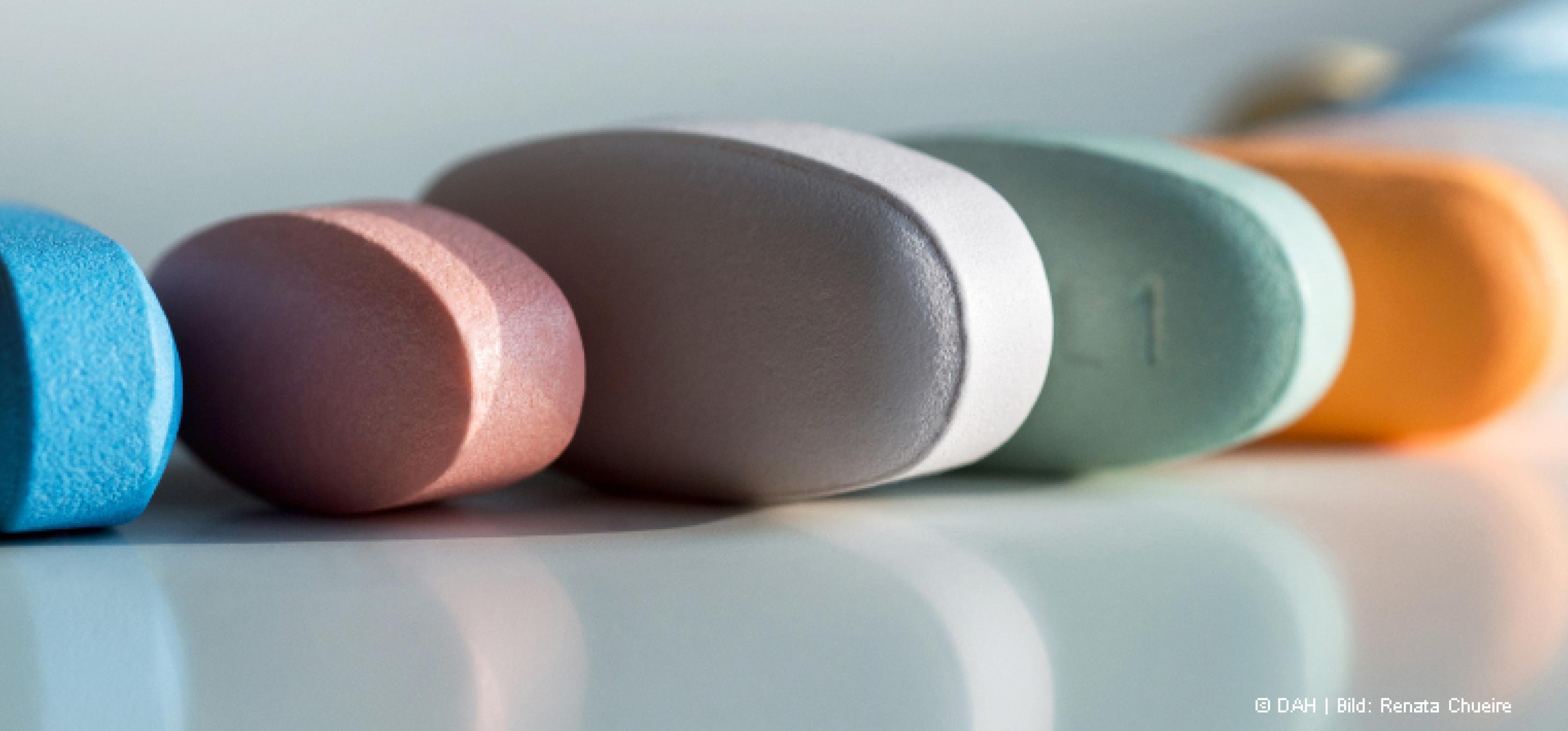 Mehrere Tabletten in verschiedenen Farben liegen aneinander gereiht auf einem weißen Tisch vor weißem Hintergrund