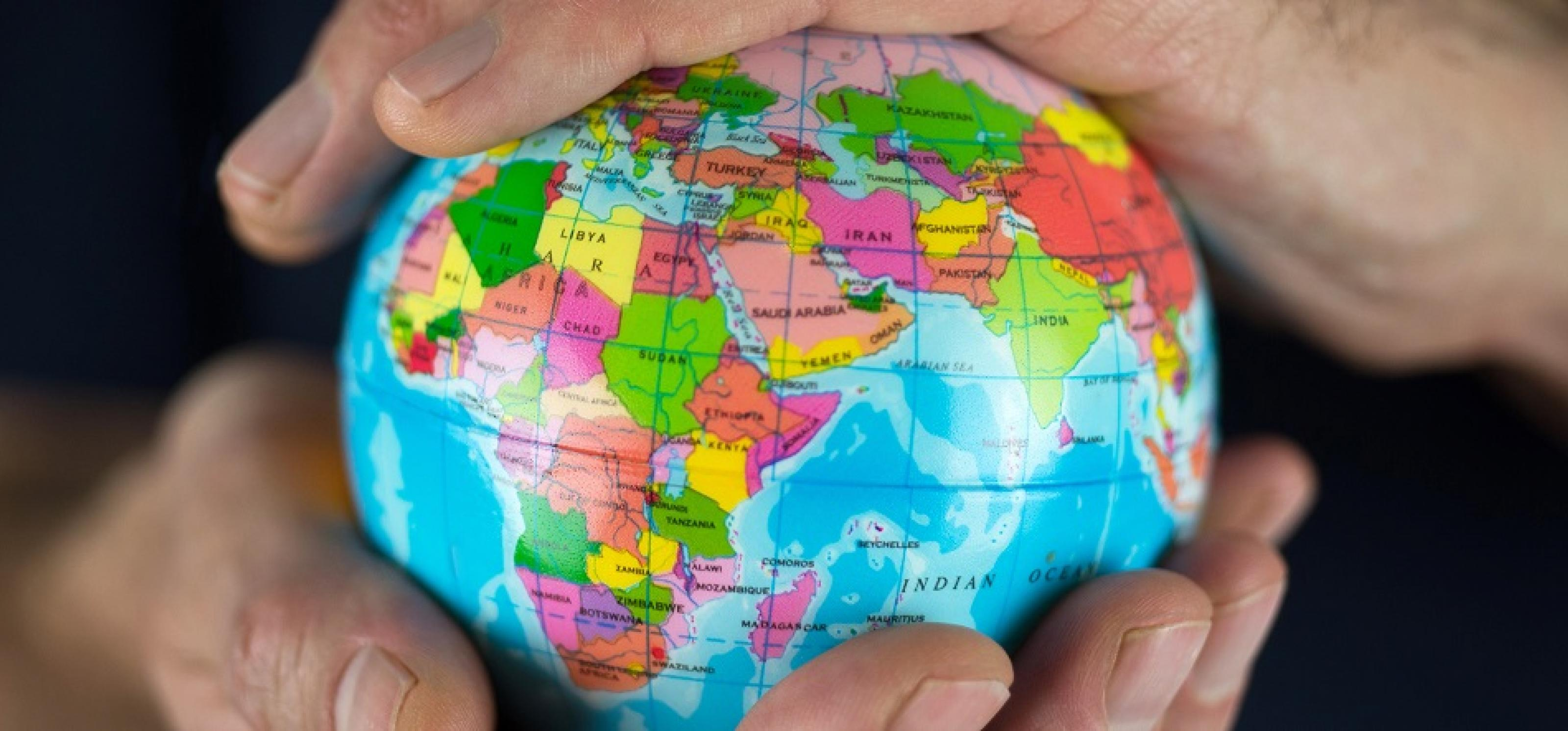 Eine kleine Weltkugel wird in zwei Händen gehalten