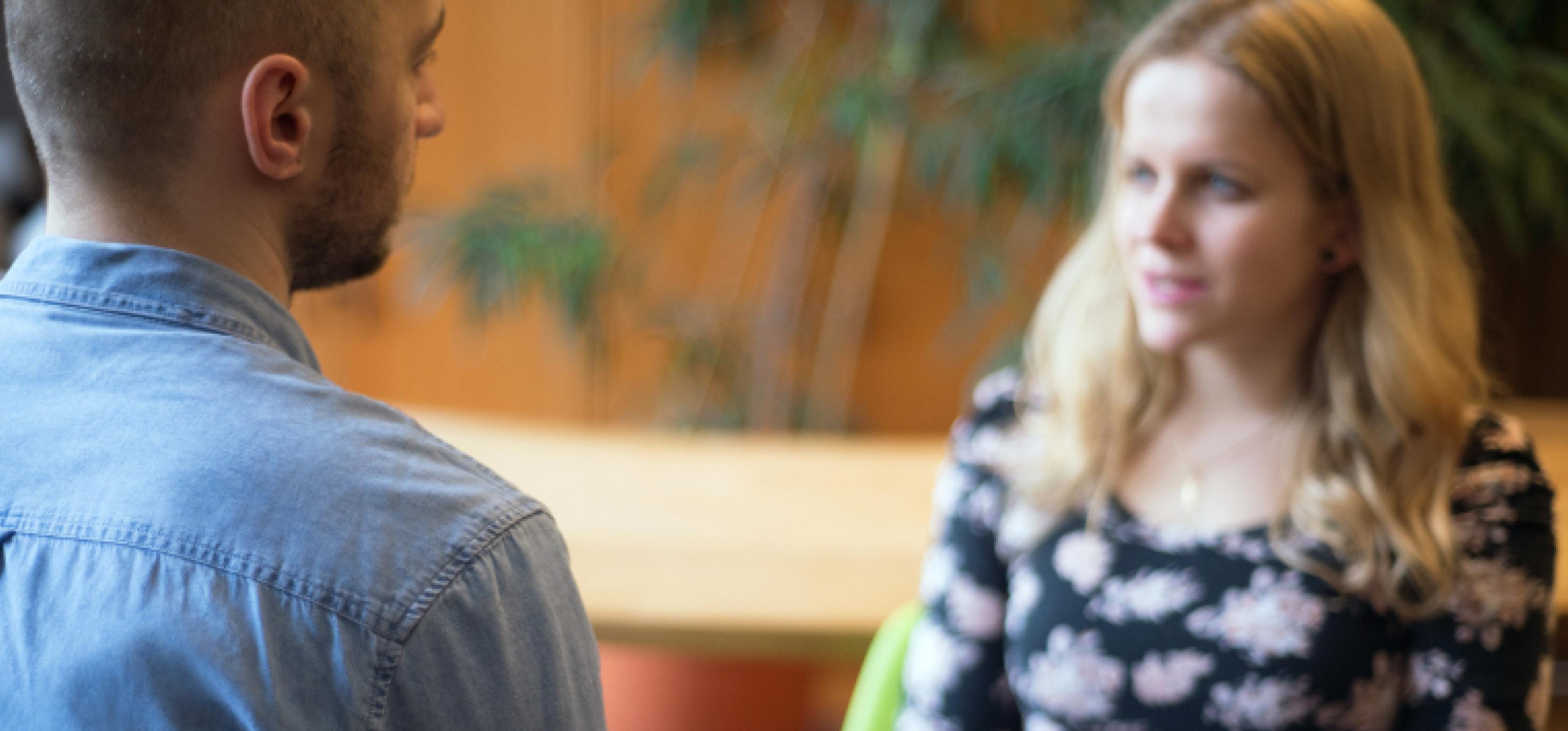 Ein Mann und eine Frau sitzen sich in einem Gespräch gegenüber.