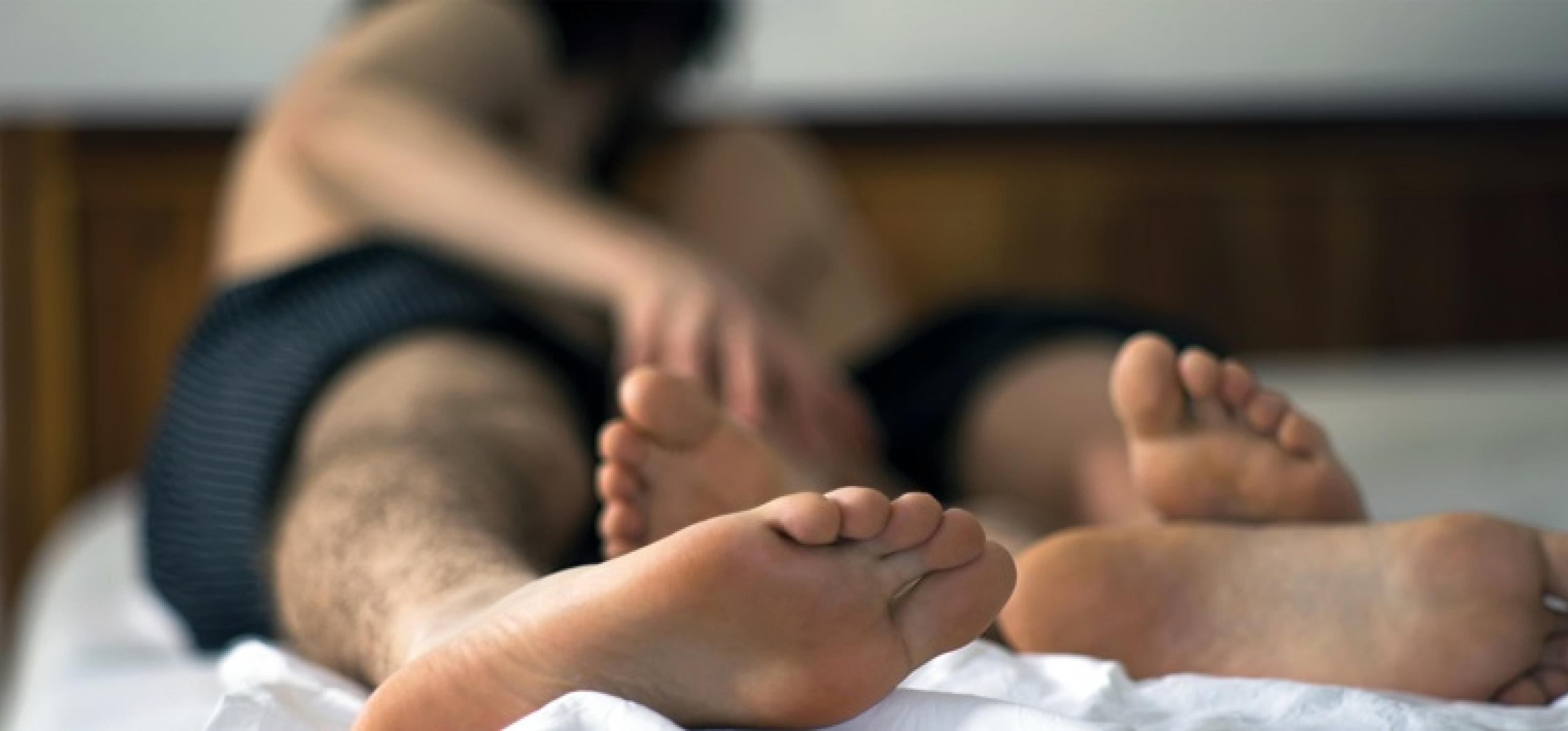 Ein Paar, bis auf die Unterhose nackt, liegt im Bett. Safer Sex