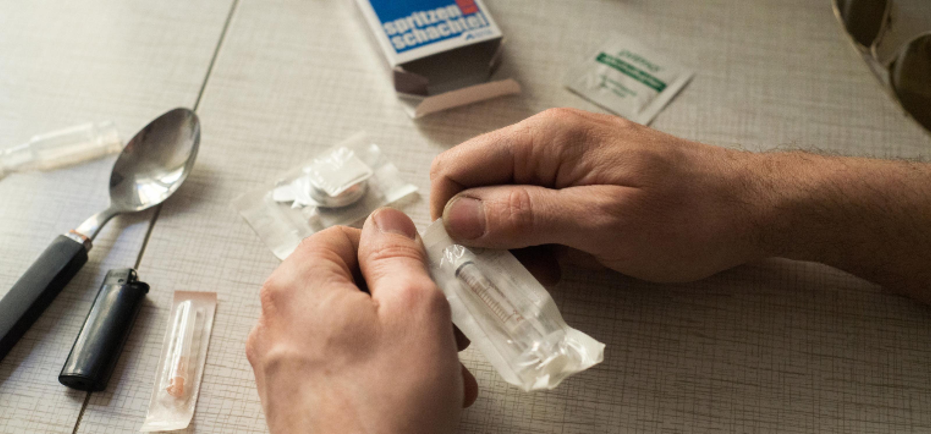 Zwei Hände öffnen die Verpackung einer steril eingepackten Spritze für Safer Use