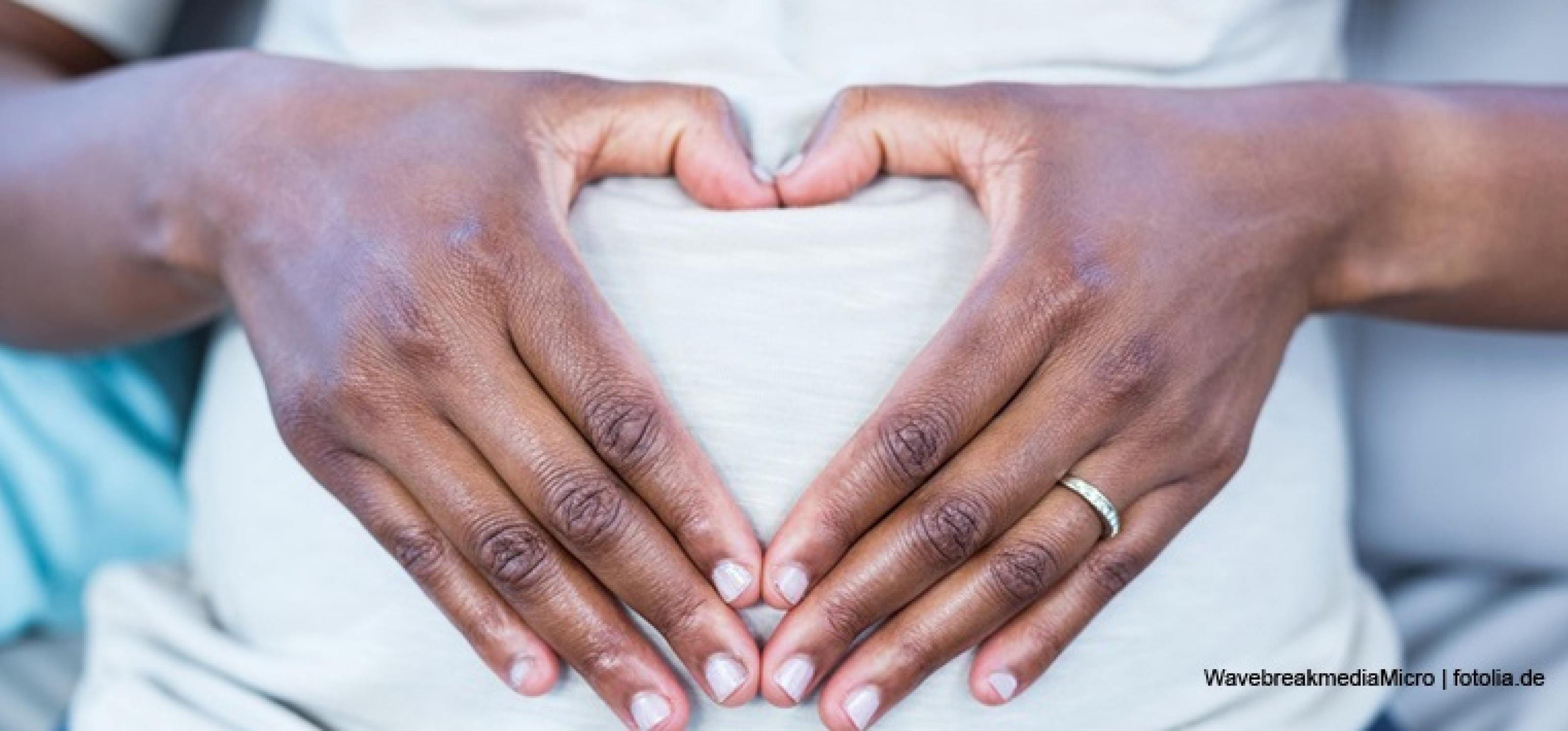 Zu einem Herzen geformte Hände vor einem Bauch